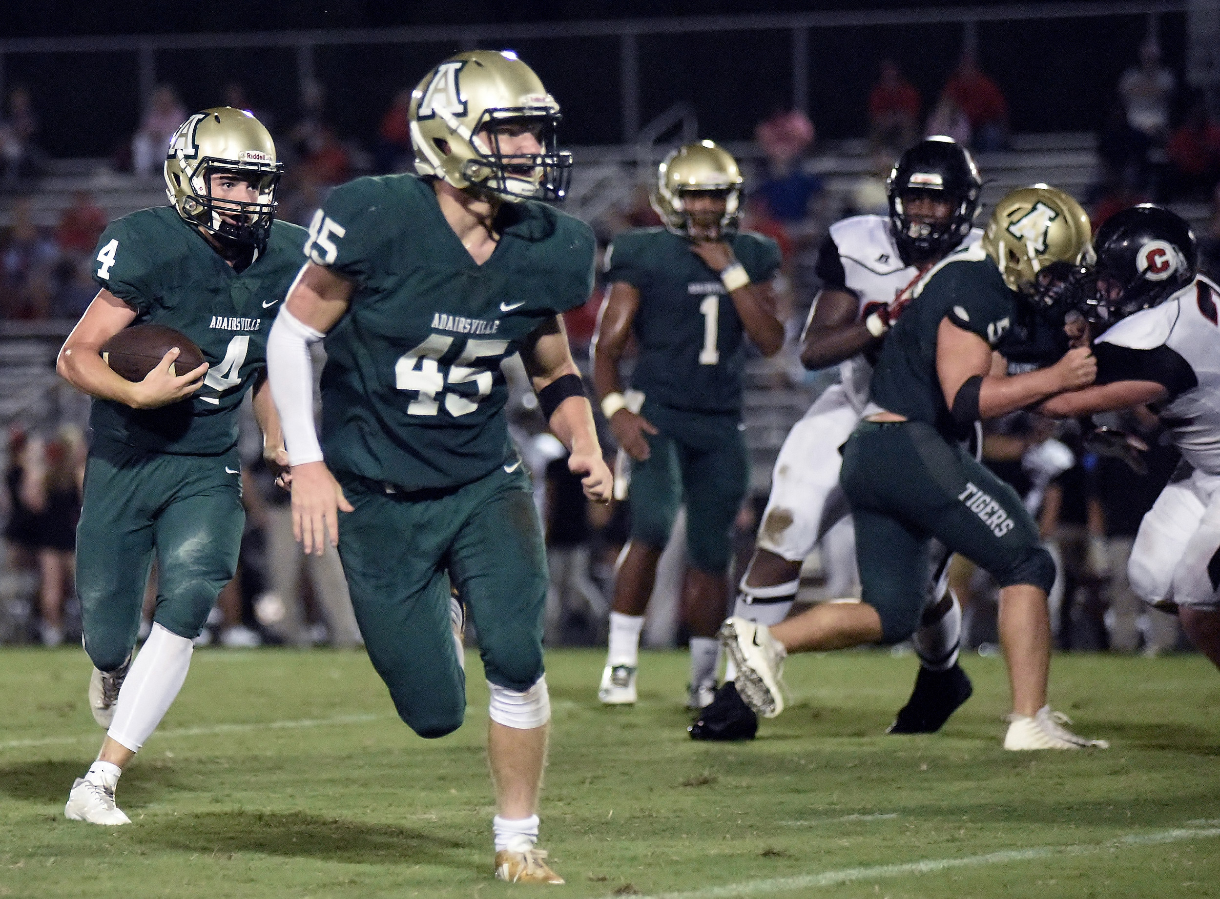 Adairsville sophomore Conner Crunkleton (4) carries the ball around the outside of the Chattooga defense, as Landon Ayers (45) looks to block and Mason Boswell (1) looks on.
