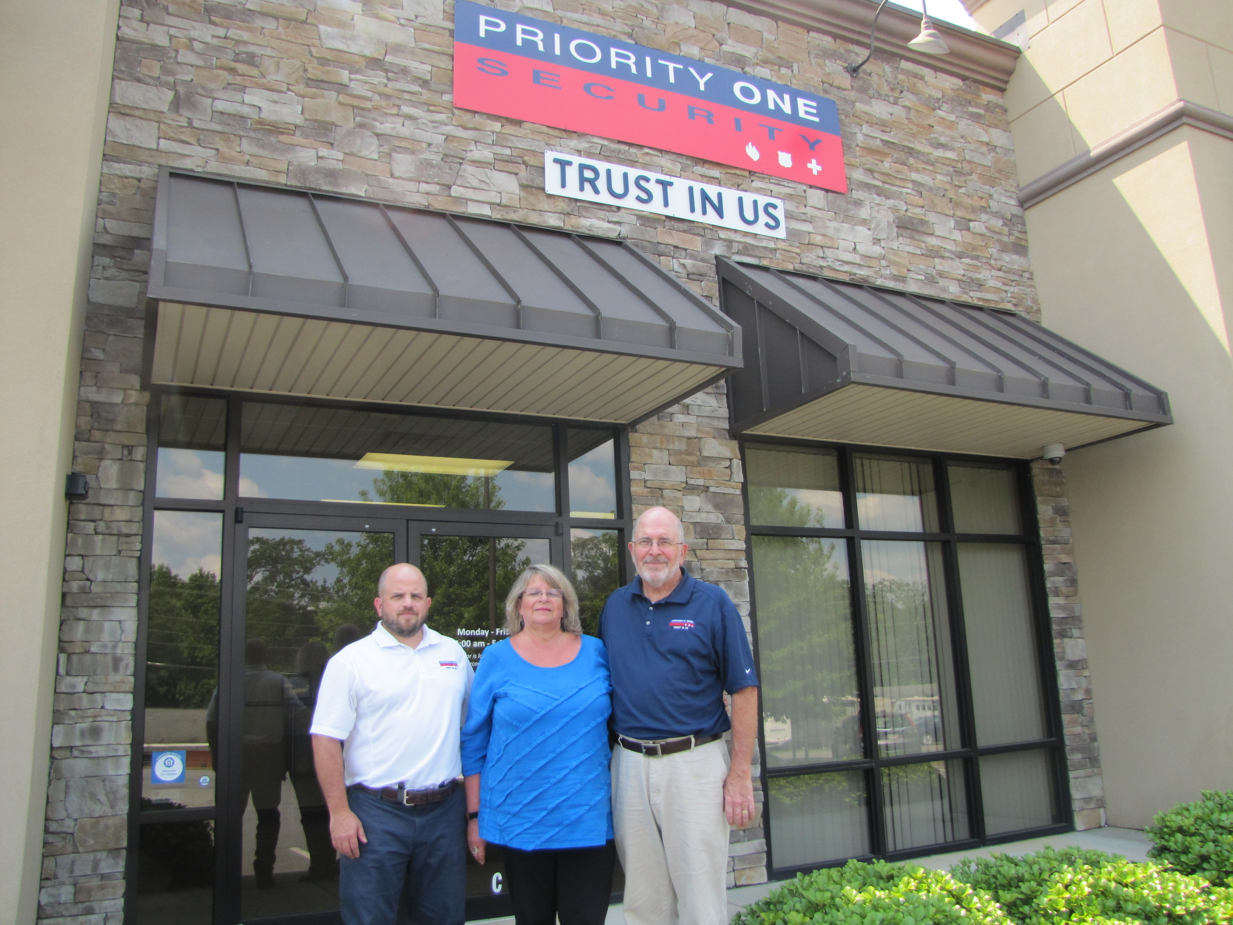 From left, Fleetwood Security personnel Evan Fleetwood, Jessica Fleetwood and Billy Fleetwood stand underneath their new corporate signage. Their business merged with Priority One Security earlier this year.
