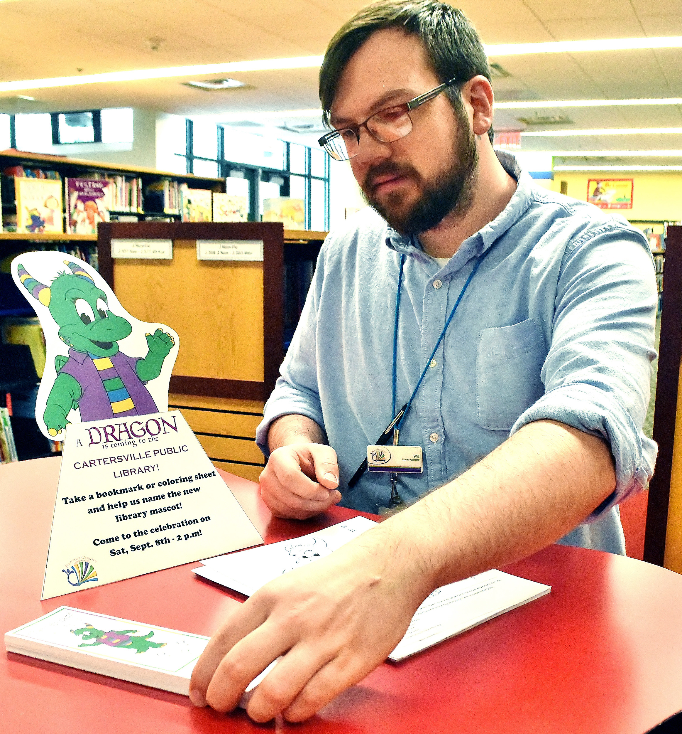 Will Gaylord, of the Cartersville branch of the Bartow County Library System, lays out materials in the children's section of the library announcing a contest to help name the dragon that has become the library's new mascot.