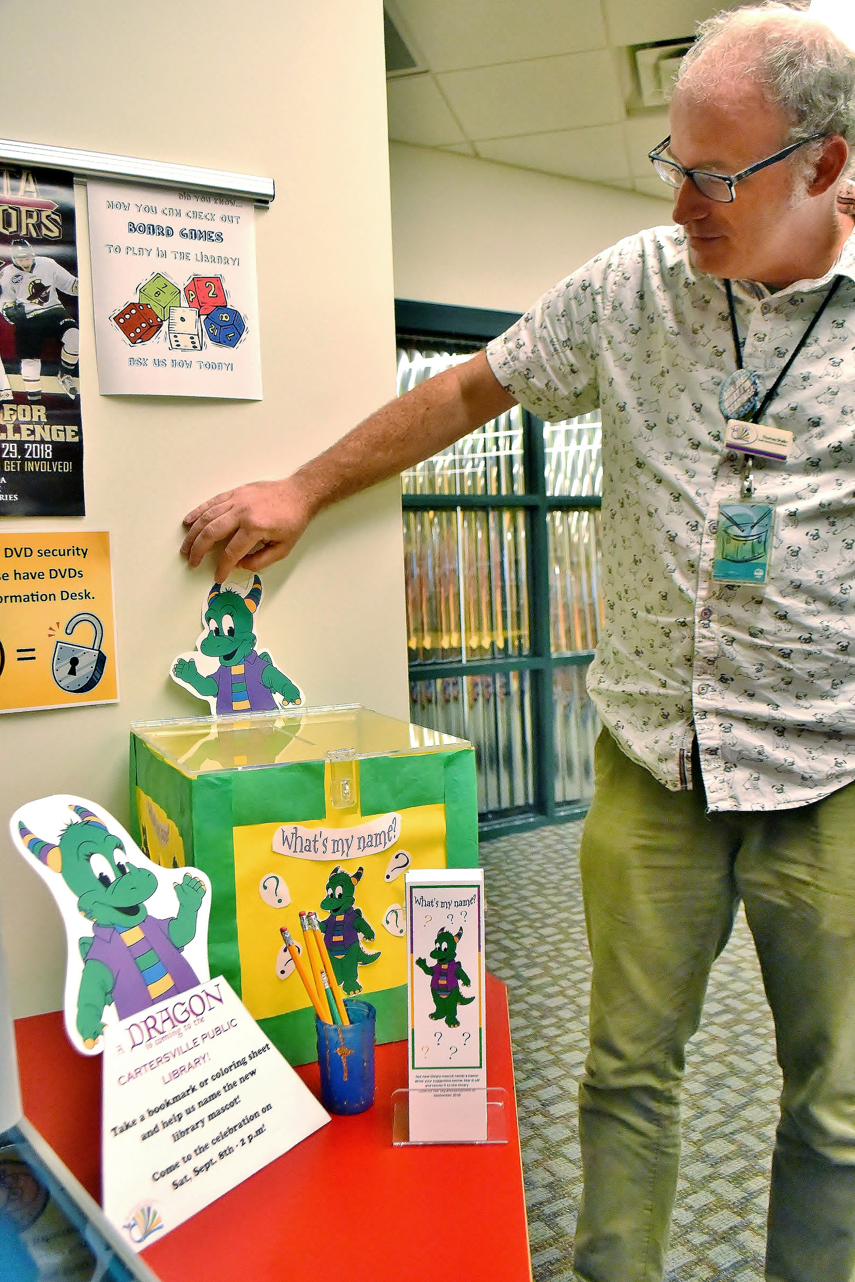 Thomas Shalin, of the Cartersville branch of the Bartow County Library System, sets up materials, including a suggestion box, in the children's section of the library for a contest to help name the dragon that has become the library's new mascot.
