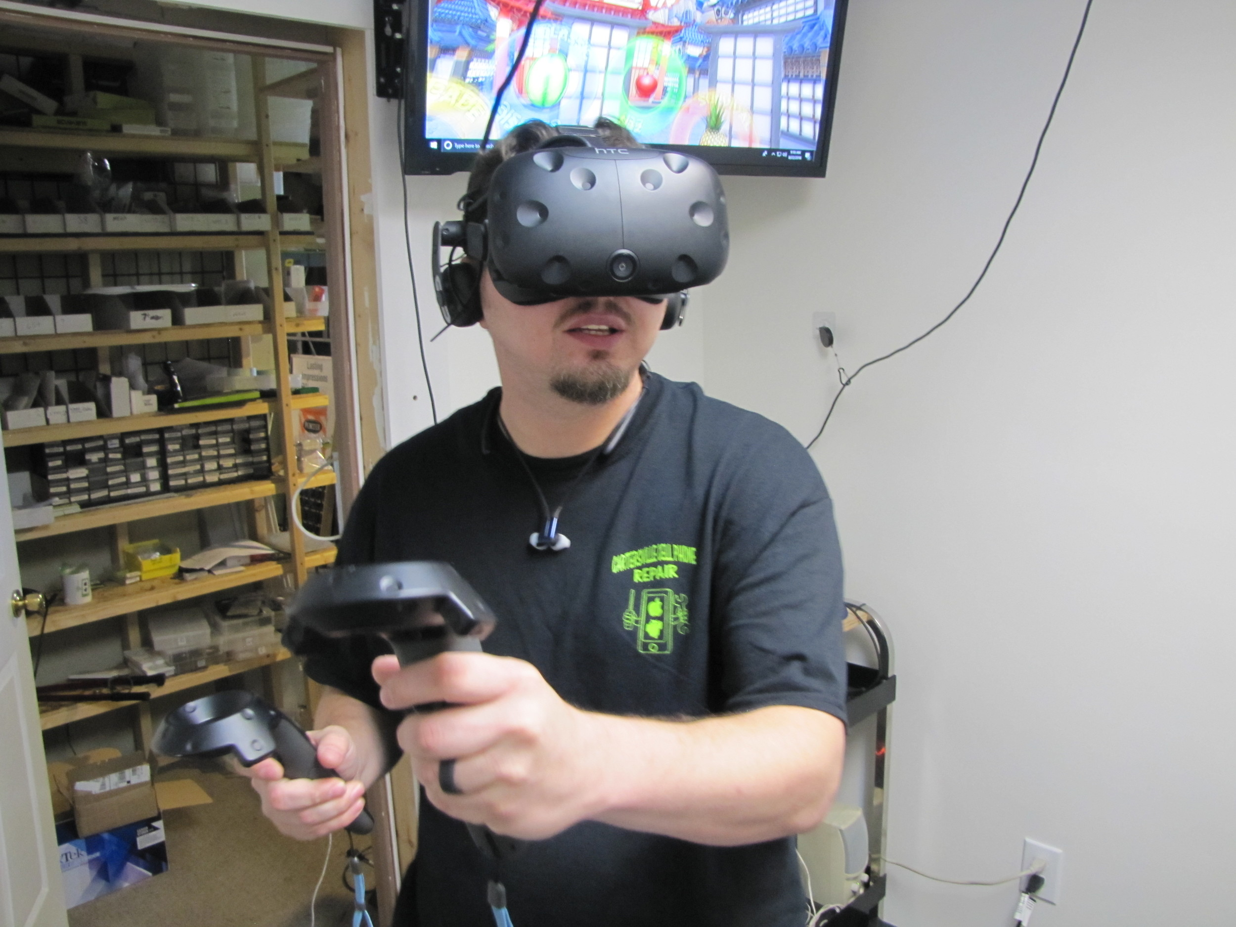 Will Neeley, lead tech at Cartersville Cell Phone Repair, demonstrates his shop's virtual reality arcade.