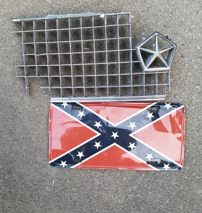 The impact knocked a piece of a Chrysler grill and a Confederate tag on the ground.