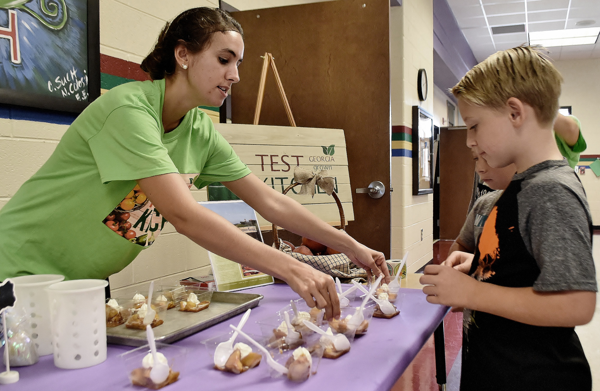 Bartow County School Nutrition Coordinator Emily Rollins serves Caramelized Skillet Peaches to Pine Log Elementary pre-K student Jameson Currie during Wednesday's Georgia Grown Test Kitchen in the school's cafeteria.