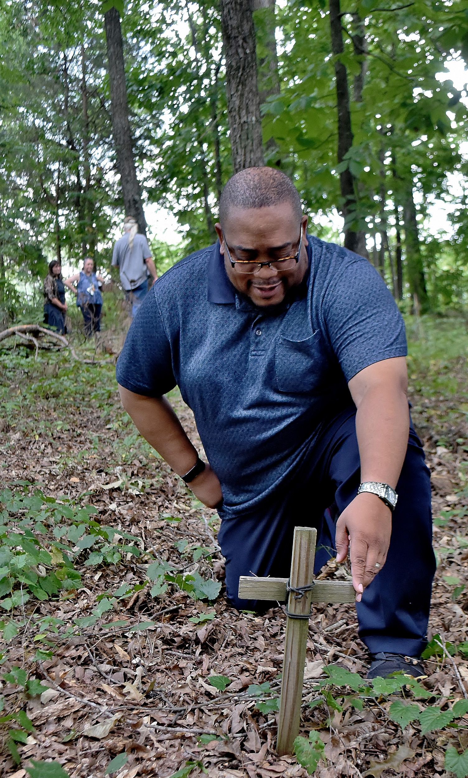 Euharlee Planning and Zoning Director Charles Reese examines one of the hundreds of wooden crosses representing a grave in the city's Black Pioneers Cemetery.