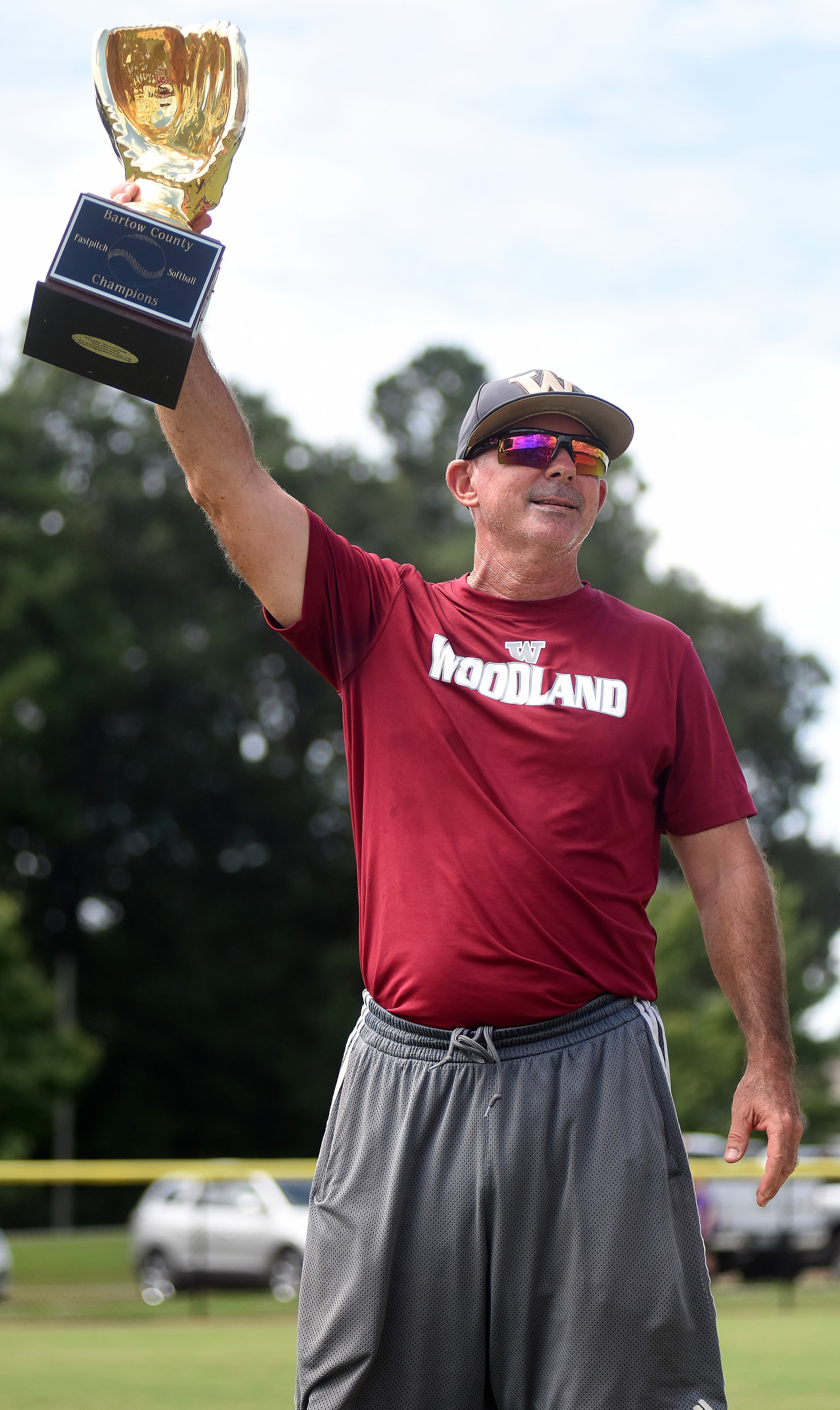 Woodland head coach Colman Roberts hoists the Bartow County Championships trophy Saturday after his team's 11-3 win over Cartersville at Hamilton Crossing.