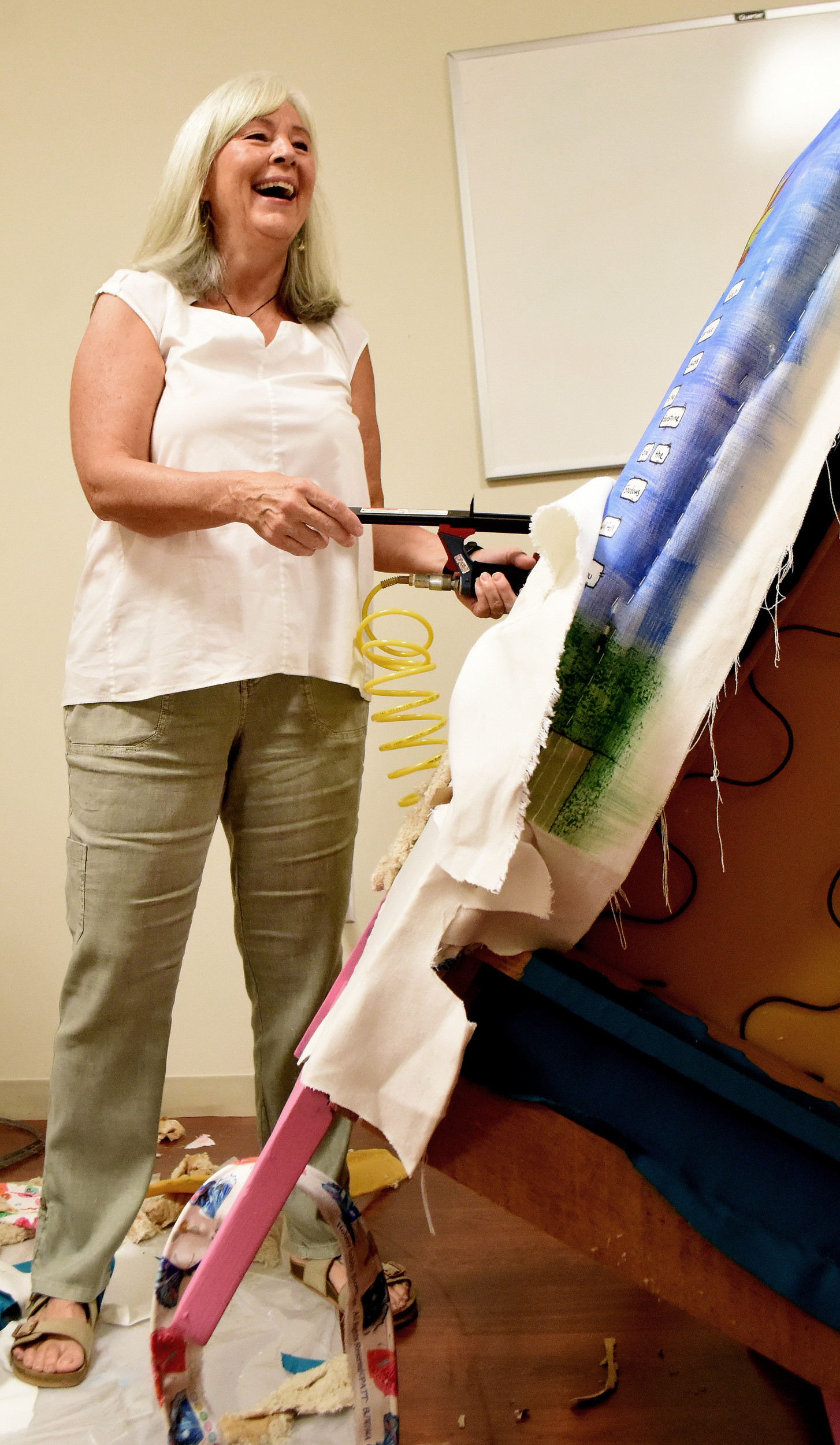 Cancer survivor Denise Conway reupholsters a chair, which will be displayed at the Survivor Dinner tent at the Relay For Life event.