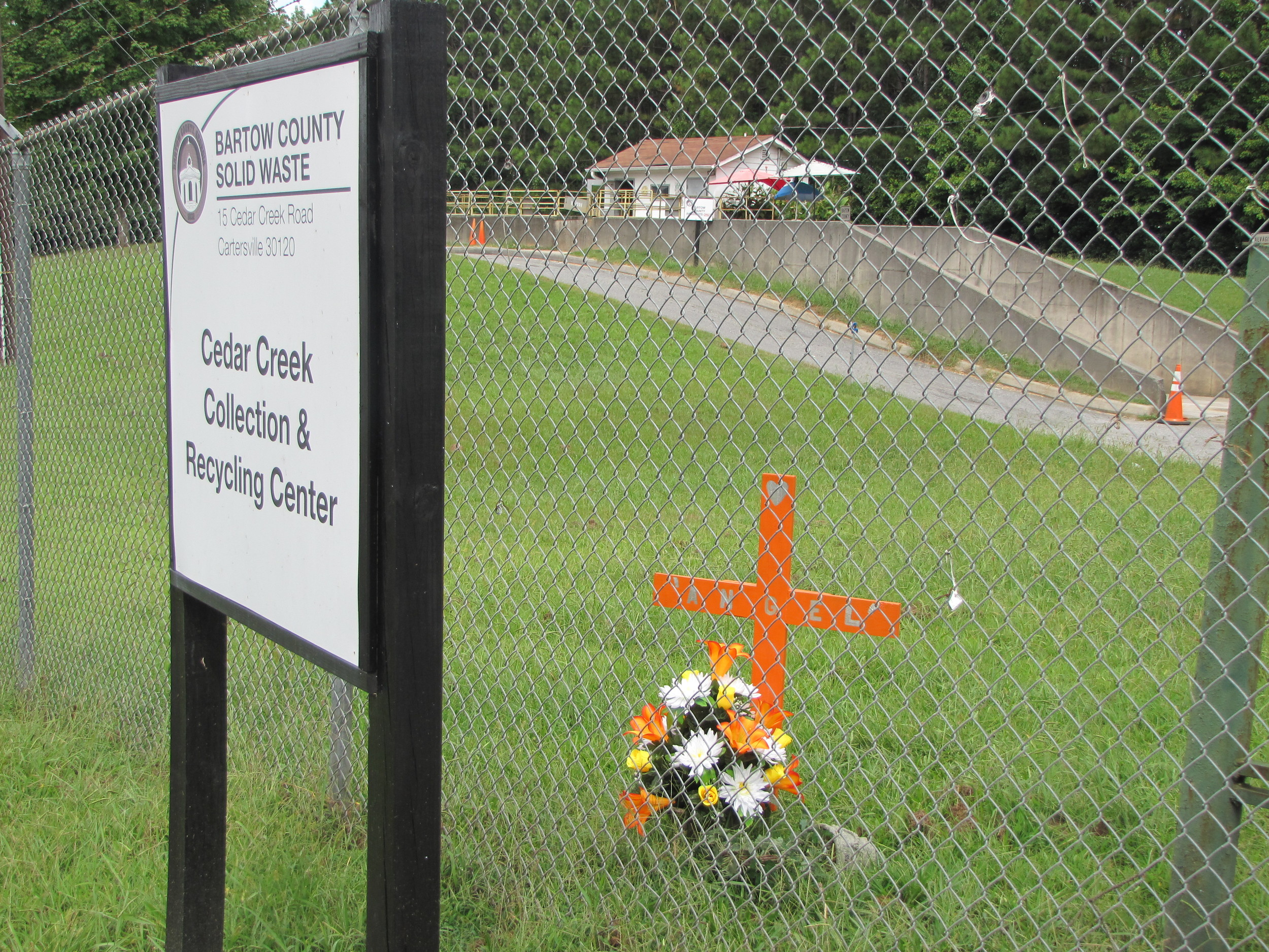 A makeshift memorial was erected at the trash compactor site where officials believe the body of a still unidentified woman was initially disposed.