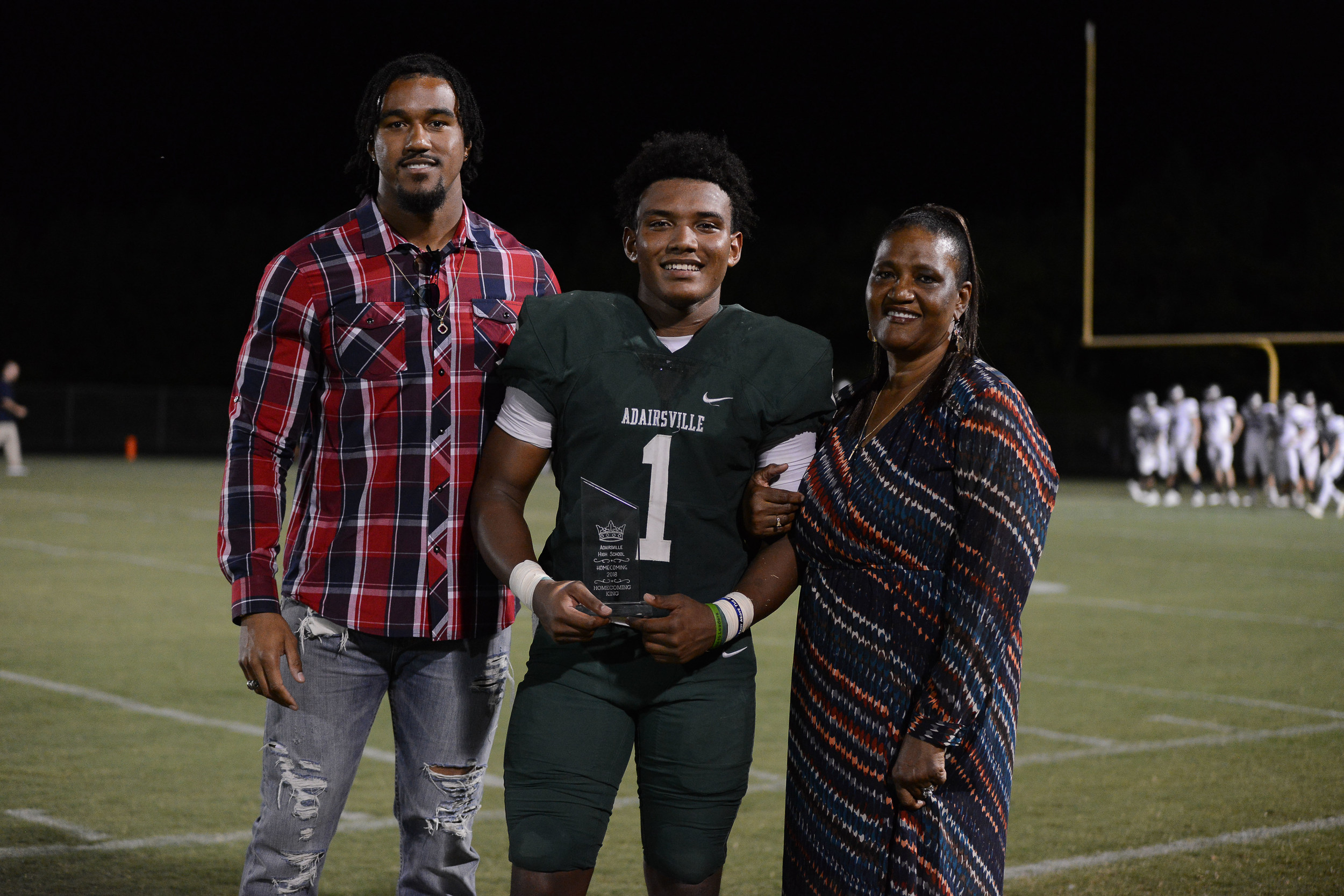 Adairsville senior Mason Boswell (1) was escorted by his cousin and Atlanta Falcons all-pro Vic Beasley, as well as Beasley's mother, Teresa, when he was named homecoming king Friday at Tiger Stadium. Boswell ran for nearly 200 yards in the win over Coahulla Creek.