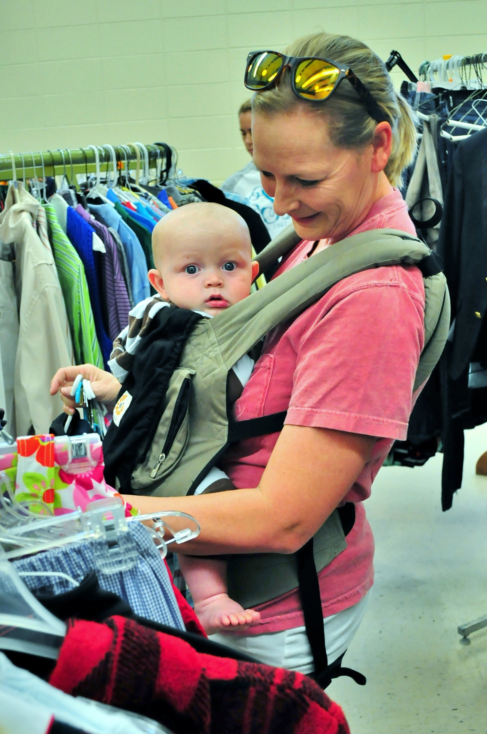 As 7-month-old Beckett waits patiently, Lauren Startup looks through items at the Cartersville Service League's Rummage Sale last year.