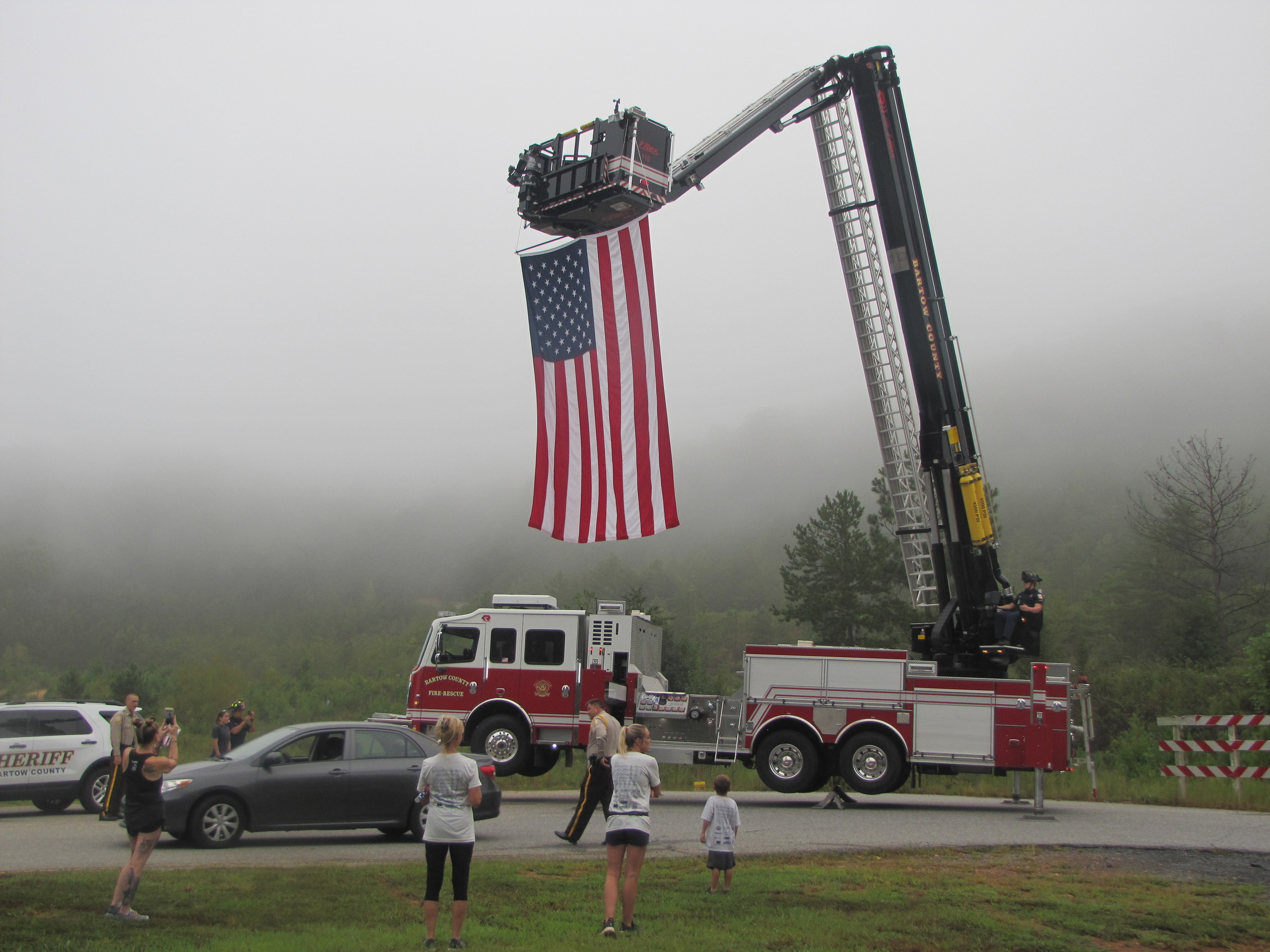 Bartow County firefighters hoist the American flag at Tuesday's March to the Mountain event in Cartersville.