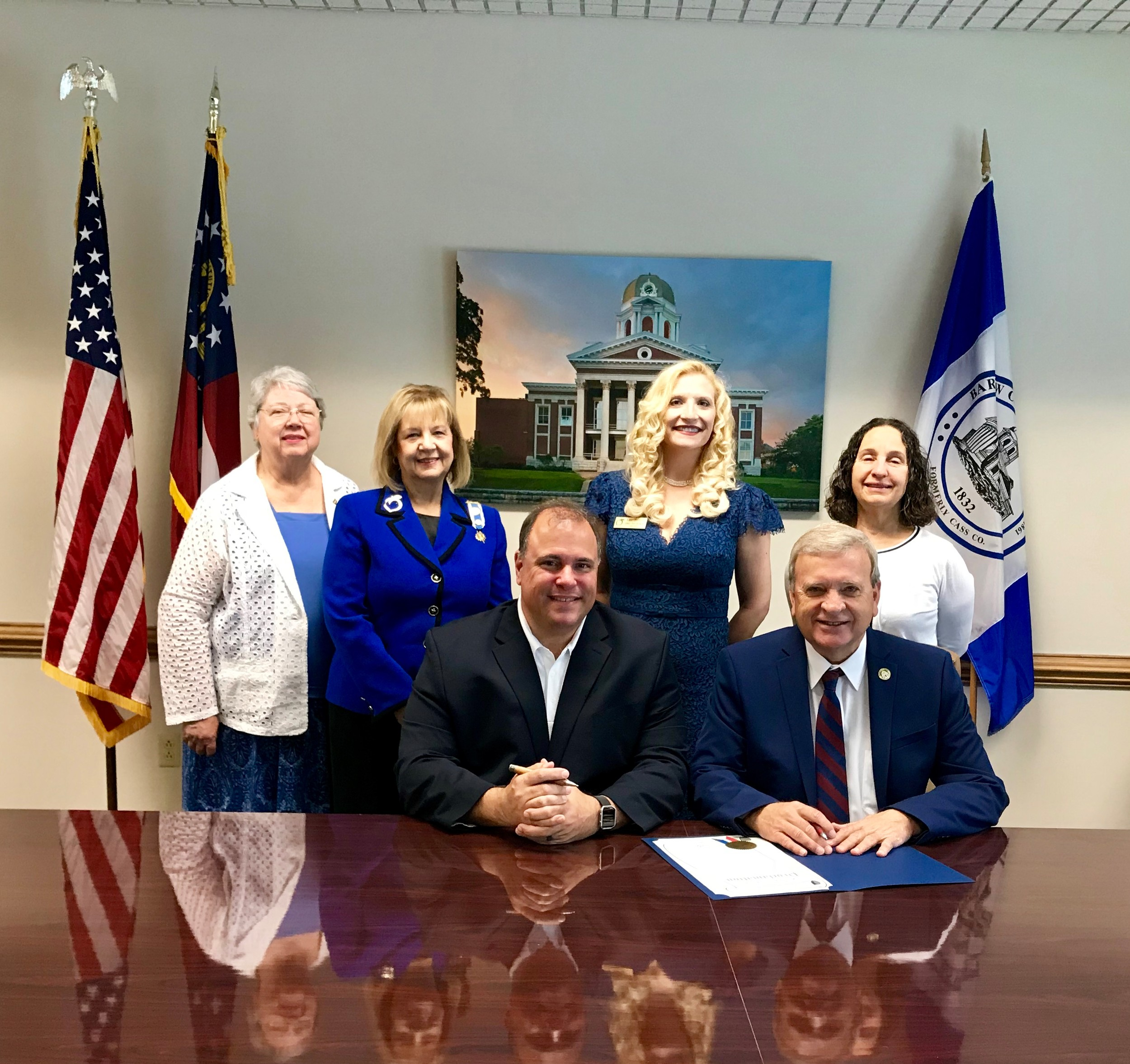 National Society Daughters of the American Revolution members, back from left, Leann Papp, Carolyn Key, Amy Nation and Beth Williams watch as Cartersville Mayor Matt Santini, left, and Bartow County Commissioner Steve Taylor sign a proclamation recognizing Sept. 17-23 as Constitution Week.