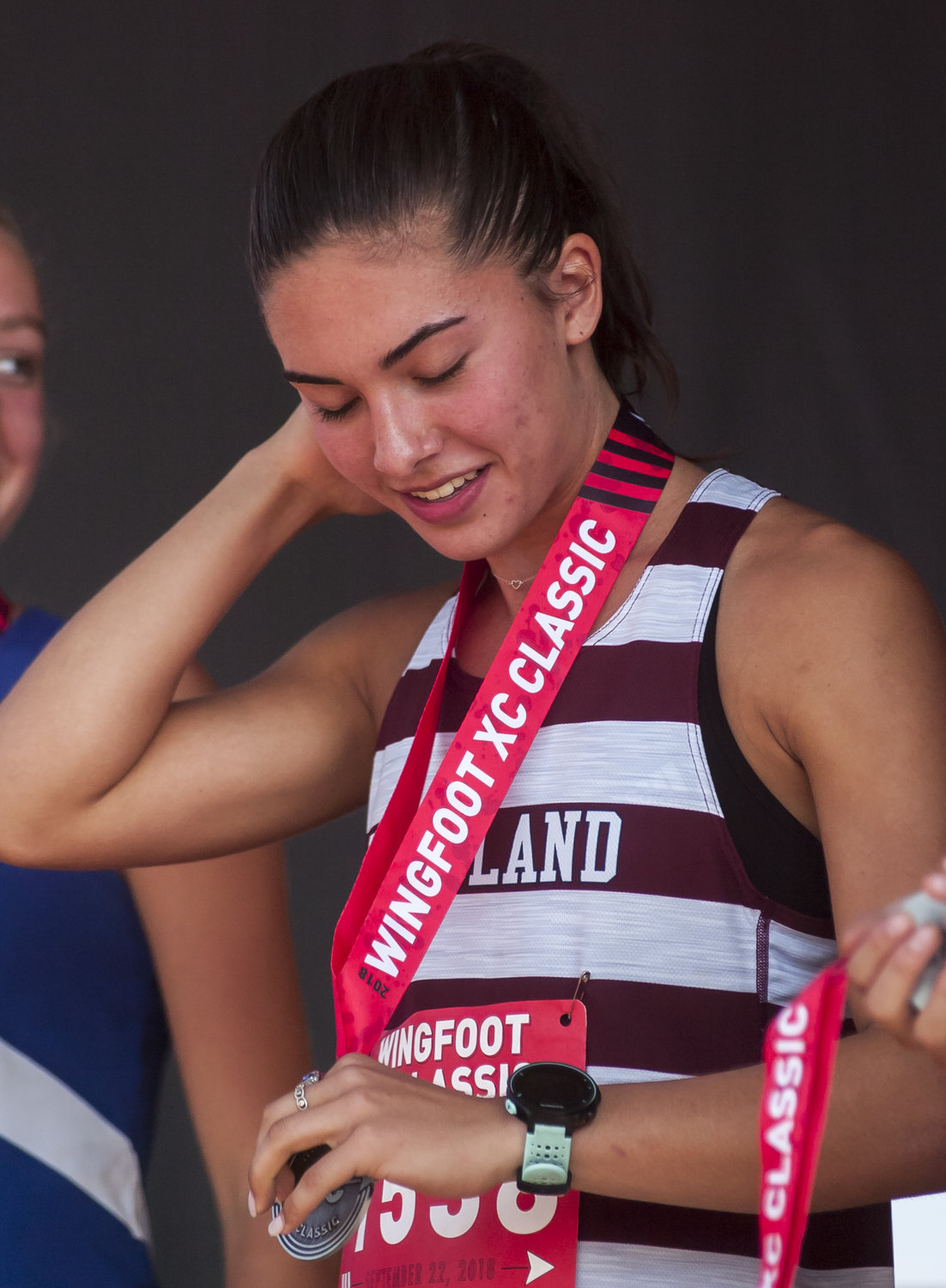 Woodland junior runner McKenna Trapheagen puts on her medal for finishing in the top 10 of the highly competitive Wingfoot XC Classic Saturday at Sam Smith Park.