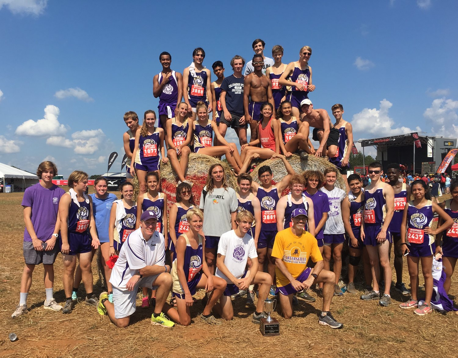 The Cartersville High cross country team poses around a bale of hay near the course of the Wingfoot XC Classic at Sam Smith Park Saturday.
