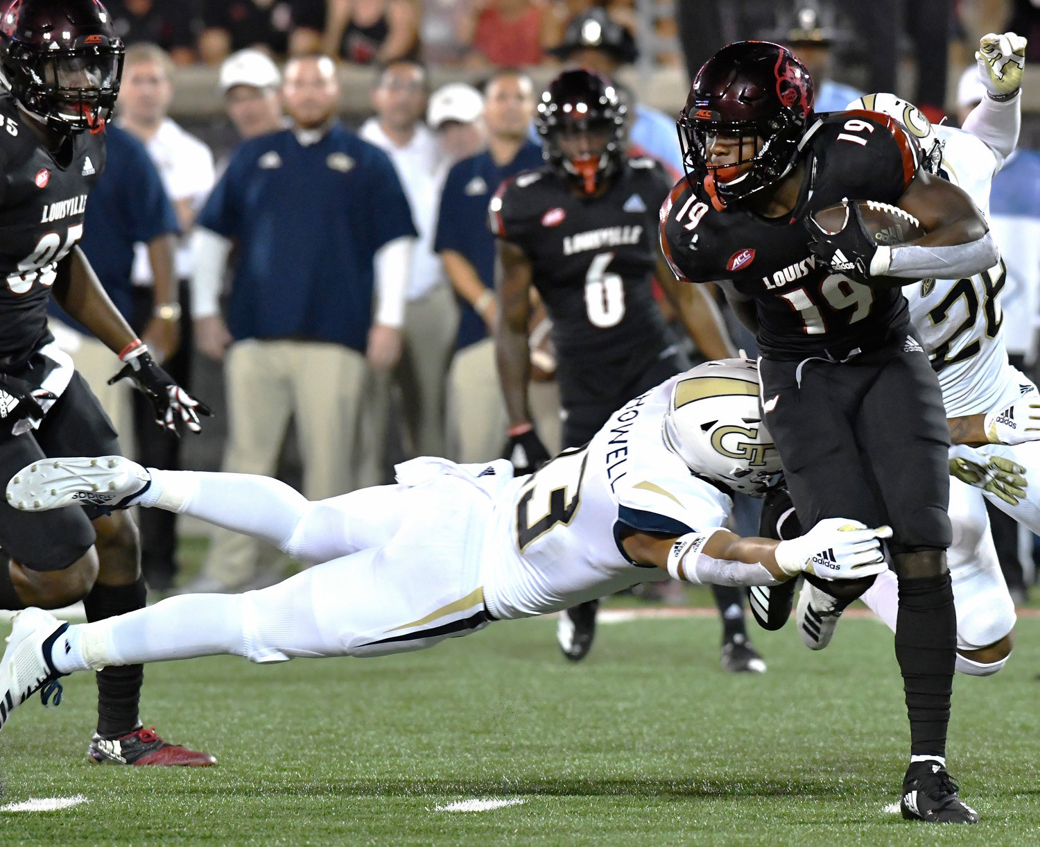 Georgia Tech defensive back and former Purple Hurricane Avery Showell (13) attempts a diving tackle on Louisville running back Hassan Hall (19) during the second half of an NCAA college football game Friday in Louisville, Kentucky.