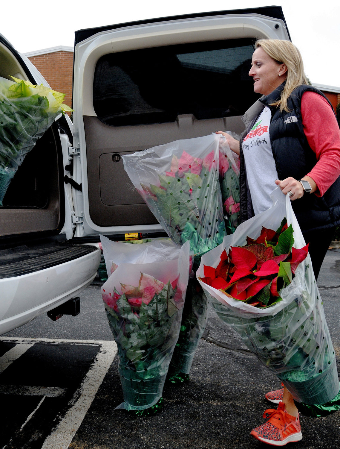 Cartersville Service League member Nicole Burns loads poinsettias into a car for delivery during last year's CSL's annual Poinsettia Sale. The event sold 2,617 plants, with the proceeds supporting various charities in Bartow County.