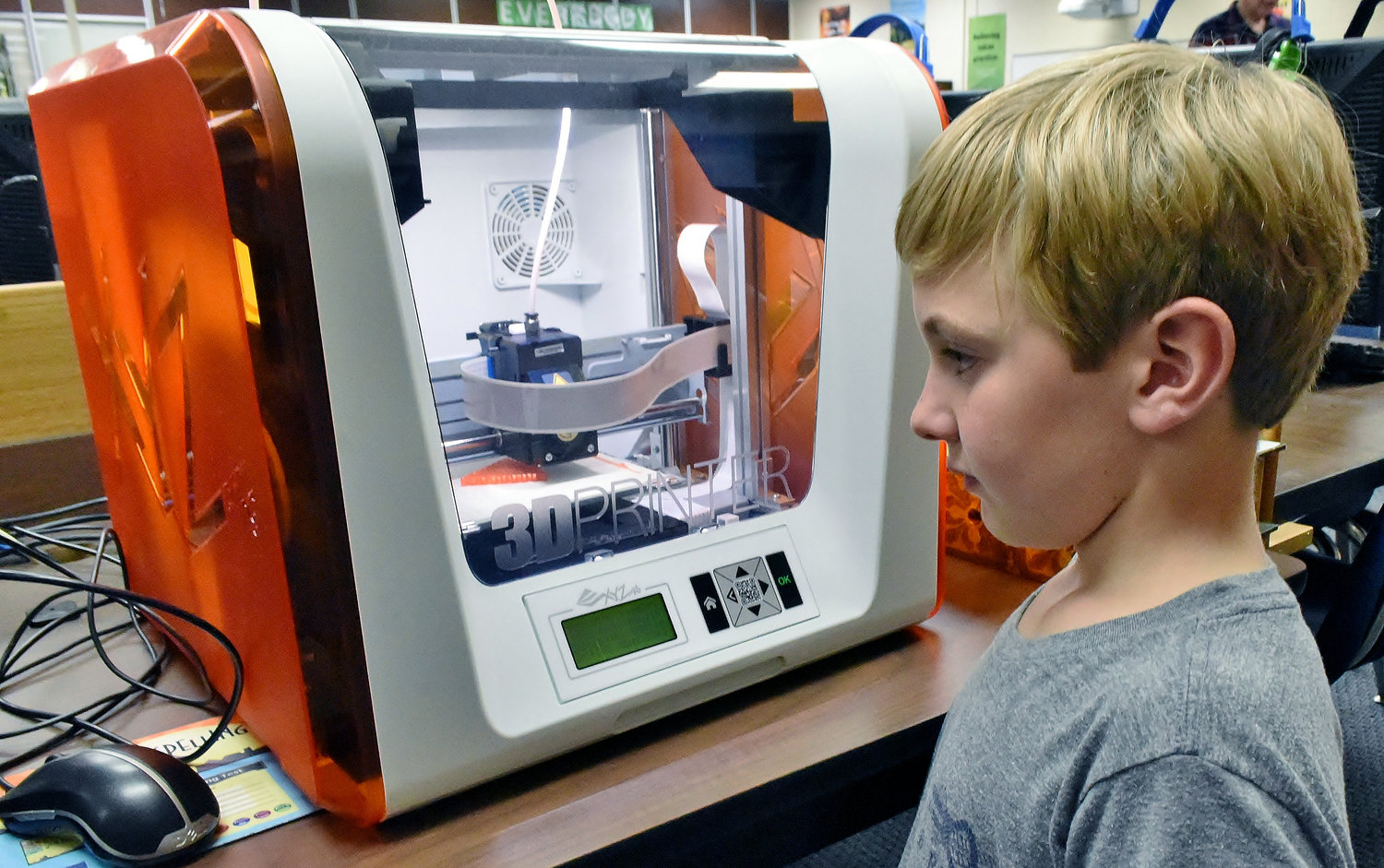 Hamilton Crossing Elementary fourth-grader Emery Holt watches as the school's 3-D printer produces a tactile 3-D symbol.