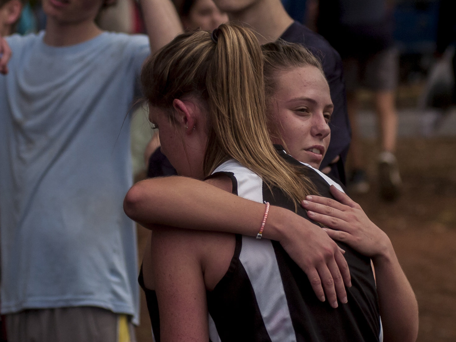 Rylee Evans hugs her big sister Baylee after the Class 5A state championship race in Carrollton Friday morning. Woodland High held on for the narrow win to secure its second state title in the last three years.