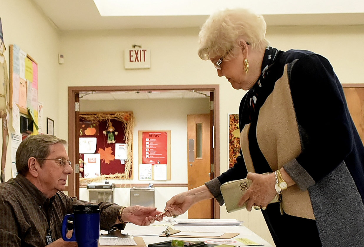 Dot Frasier presents her photo identification to poll worker L.D. Waters at the Zena Drive senior center voting precinct Tuesday.