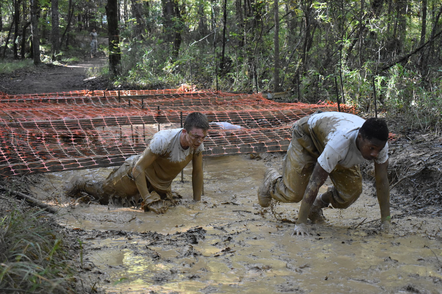 Angel Banda, left, and Brandon Bosdell, members of Adairsville High's male Raiders team, crawl out of the mud pit during the Cross Country Rescue event at the National Raider Championships in Molena Saturday.