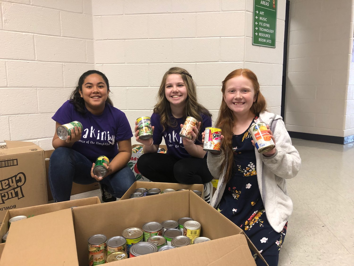 Clear Creek Elementary students, from left, Emely Melendez, Briley Hailey and Amelia Carter fill boxes with canned goods their school collected during a food drive for The Salvation Army and North Bartow Community Services last month.