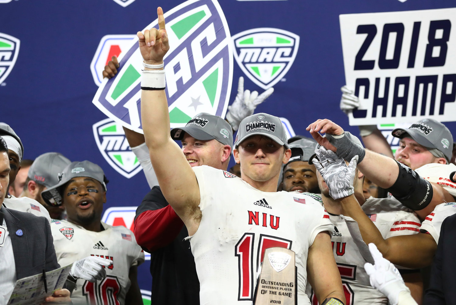 Northern Illinois quarterback Marcus Childers, holding the MAC Championship outstanding offensive player of the game trophy, points to the crowd after leading NIU to a come-from-behind victory in the conference championship game against Buffalo Friday in Detroit.