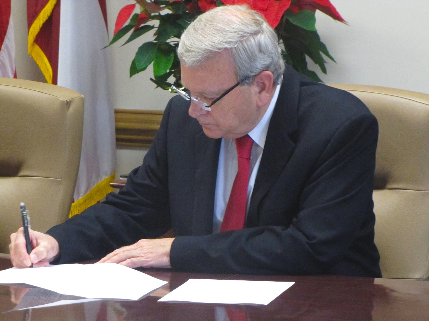 Bartow County Commissioner Steve Taylor inks documents at Wednesday's public meeting. Among other items, he approved the creation of the Etowah-Allatoona Economic Corridor, which includes 32 parcels in and around Emerson.