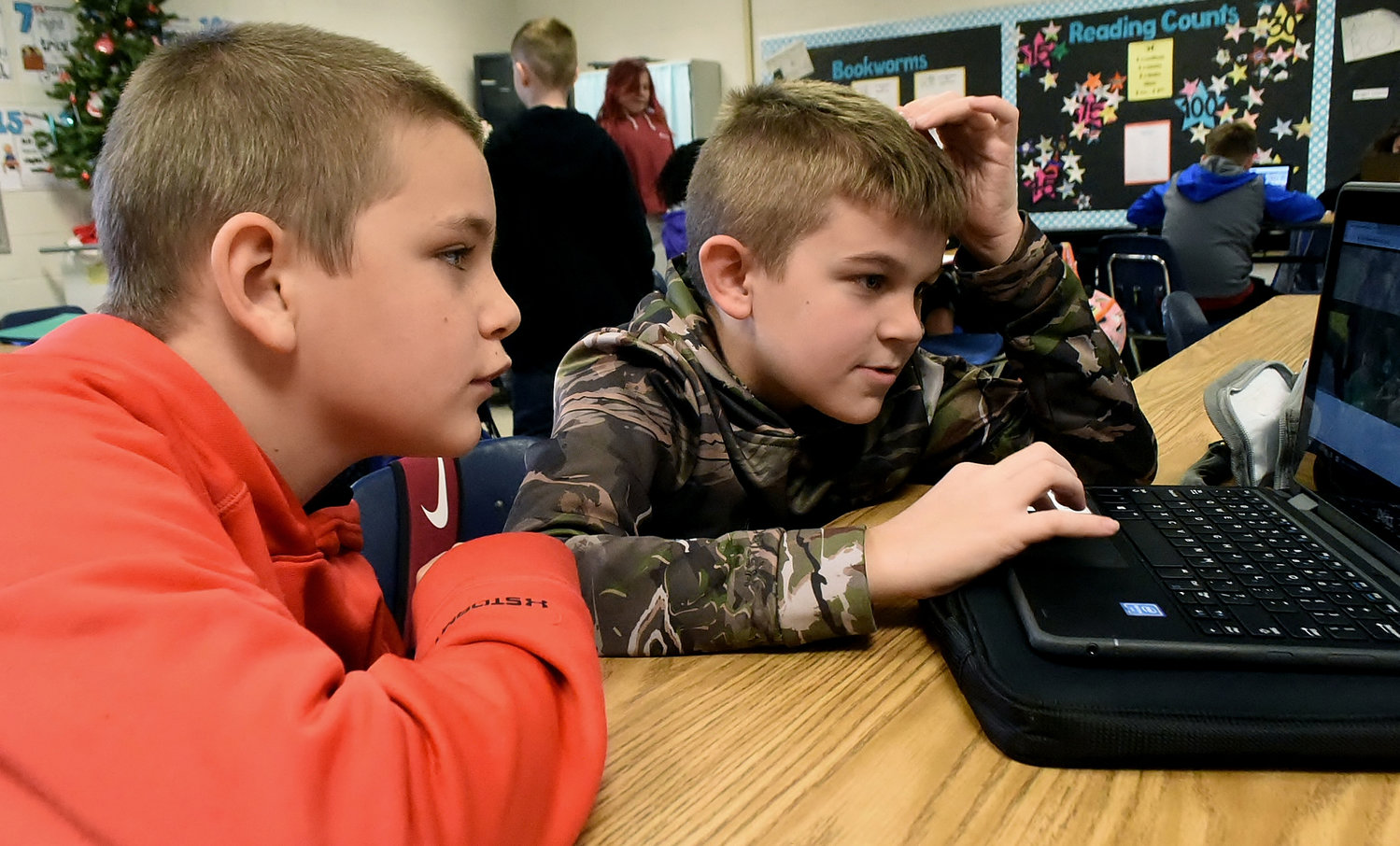 Clear Creek Elementary fifth-graders Okie Ellinger, left, and Cotton Cox code an interactive video game during Hour of Code activities Tuesday.