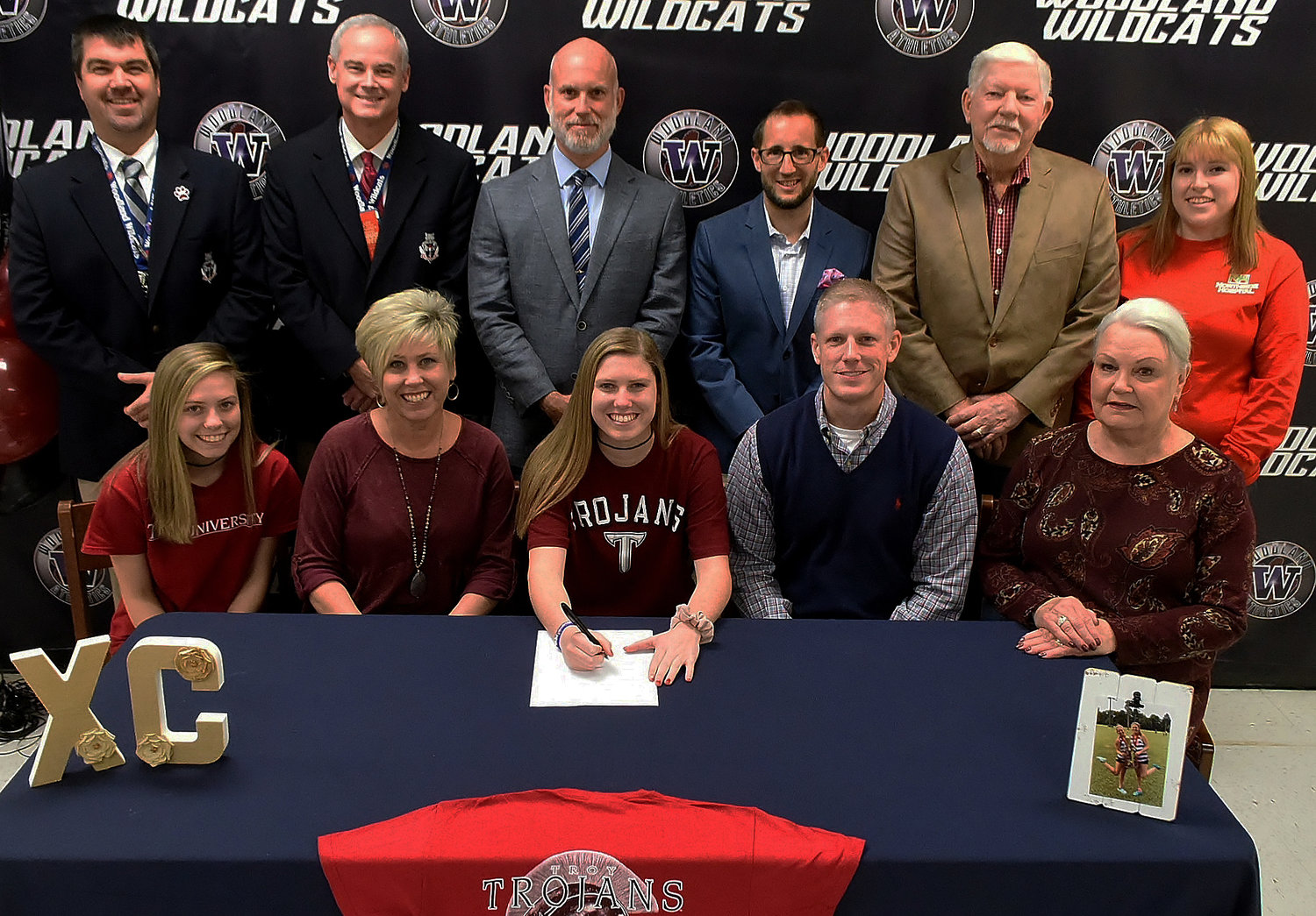 Woodland High senior Baylee Evans, center, signed Tuesday to run cross country at Troy University in Troy, Alabama. On hand for the signing were, from left, front row: Rylee Evans, sister; Stacey Evans; mother; Doug Evans, father; Glenda Evans, grandmother; back row: John Howard, WHS assistant principal and athletics director; Wes Dickey, WHS principal; Rob Forbes, WHS boys cross country coach; Matthew Landolt, WHS girls cross country coach; Ronnie Evans, grandfather; and Katie Langham, cousin.