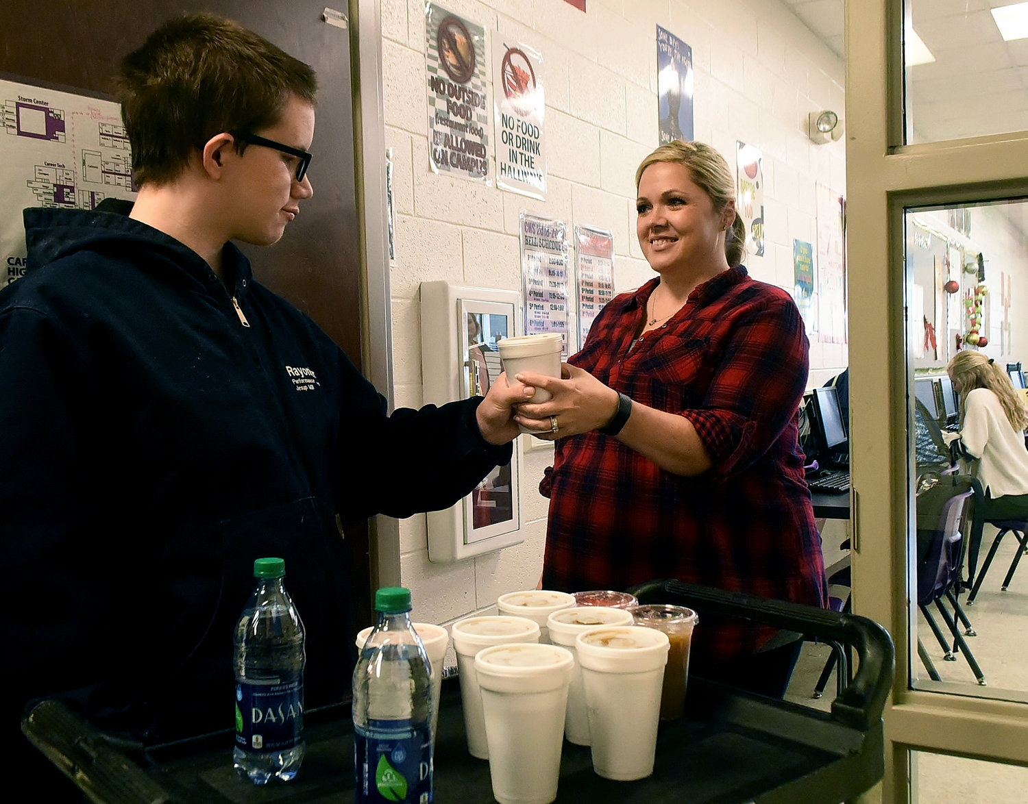 Jack Phillips, a student at Cartersville High School, delivers a cup of coffee to marketing teacher Camille Spradley at her classroom Thursday morning as part of the Canes Cups program.