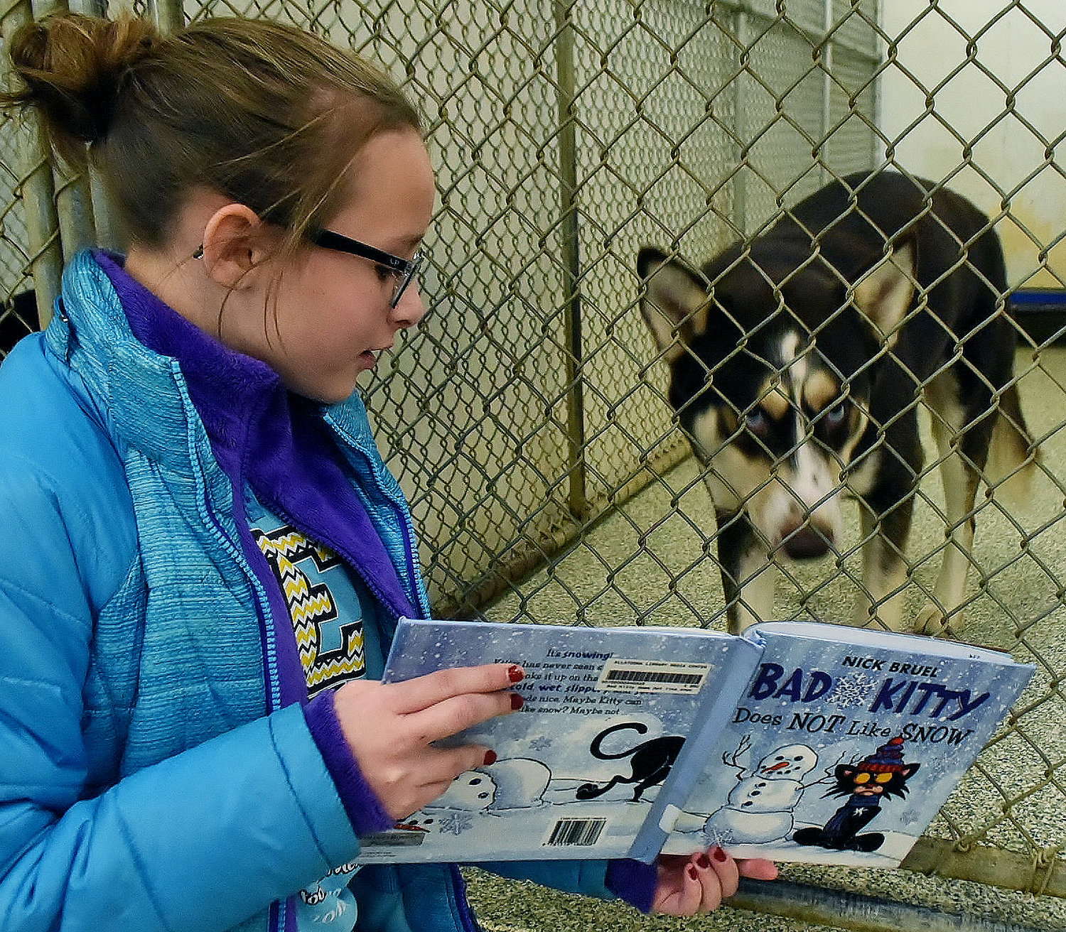 Allatoona Elementary School fifth-grader and Junior Beta Club member Aubreey Donnelly reads to Cooper, a dog available for adoption at the Etowah Valley Humane Society shelter in Cartersville.