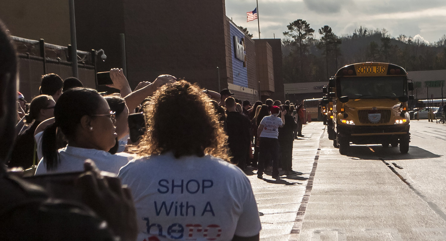 Participants in Saturday's Shop with a Hero event record the arrival of the shoppers outside Walmart.