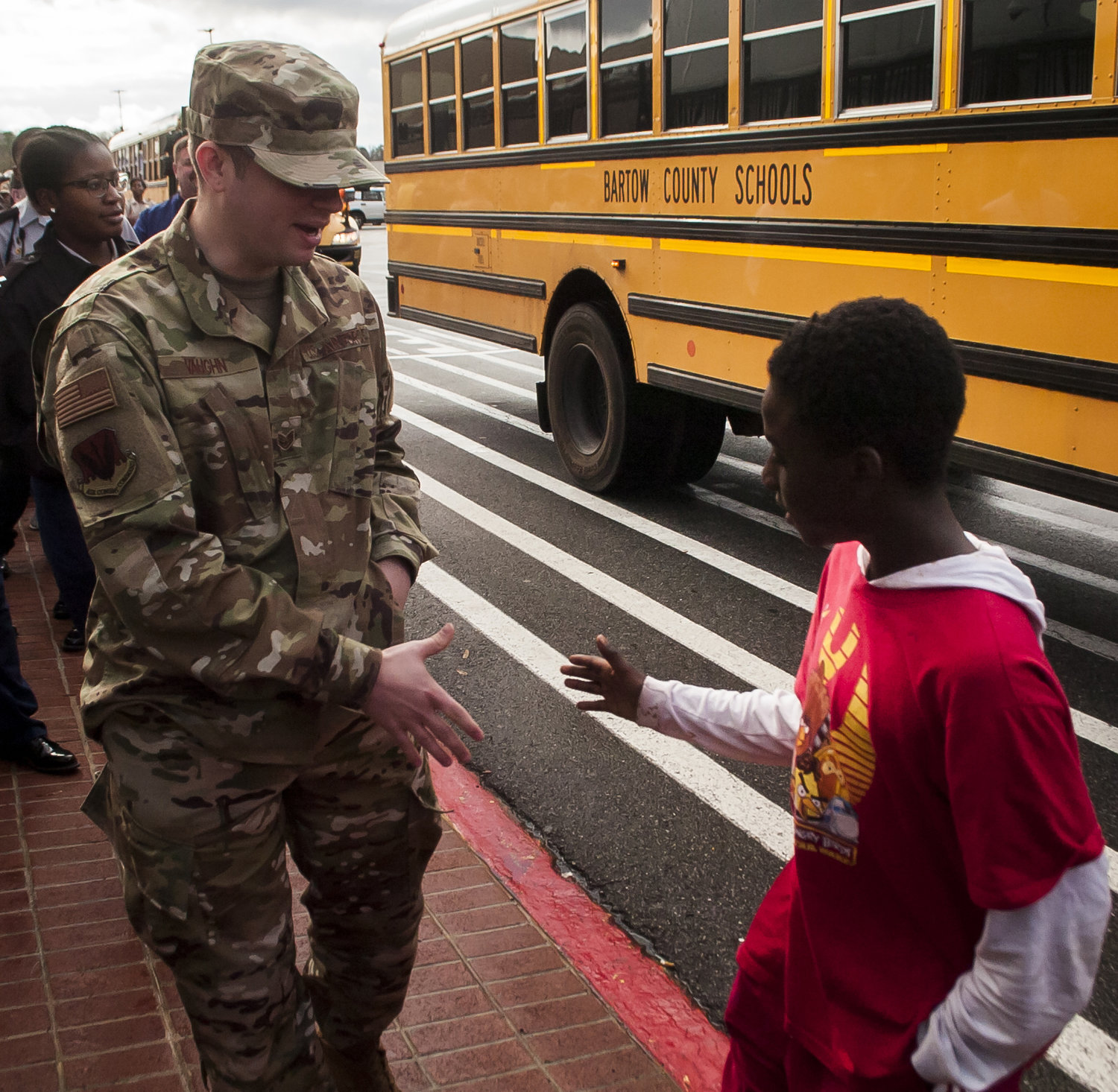 U.S. Air Force Sgt. Andrew Vaughn greets his shopper for Saturday's Shop with a Hero event, Jelani Weather, after Weather gets off the bus at Walmart.