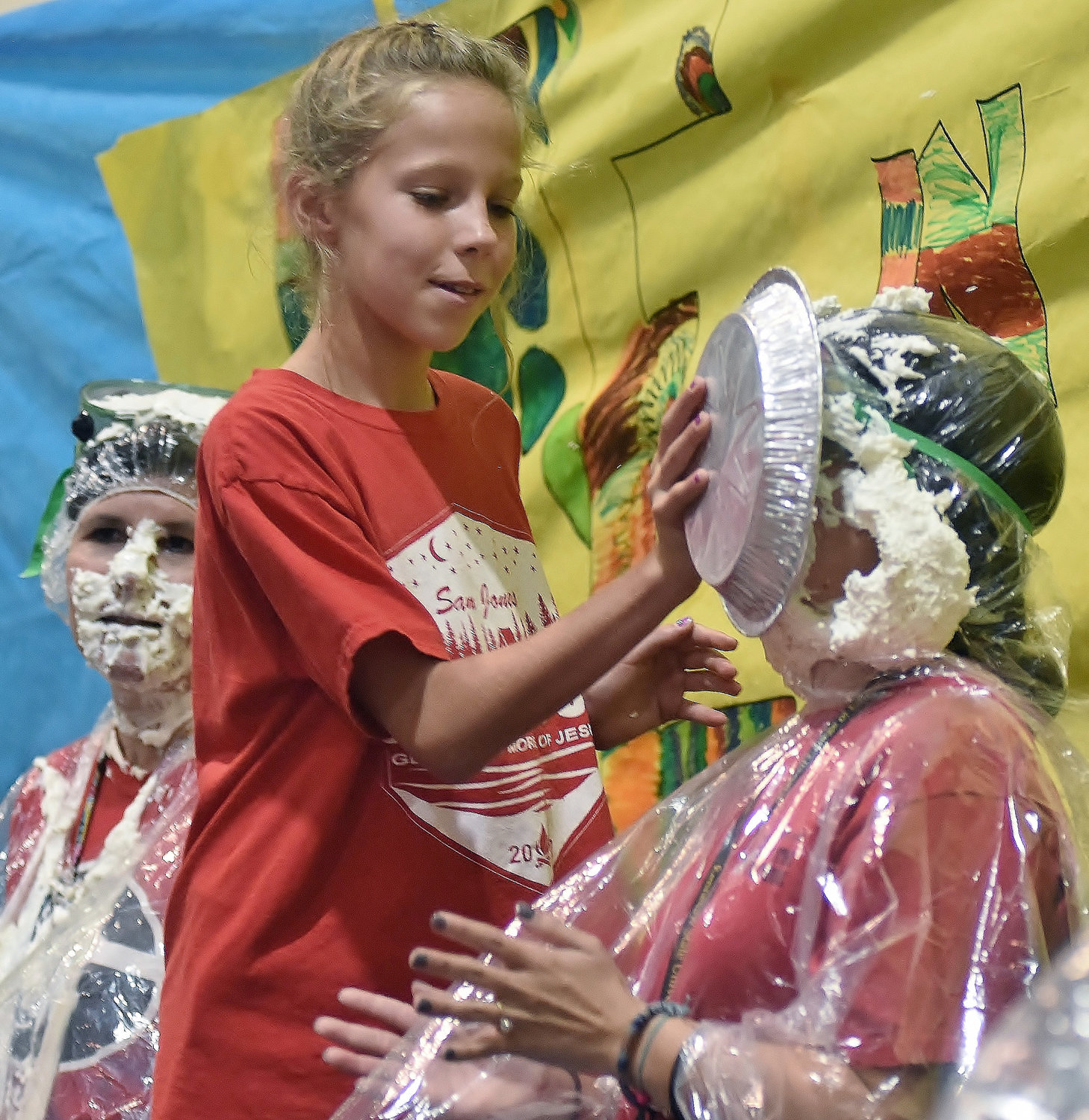 After Hamilton Crossing Elementary School teacher Jen Colston, left, took a pie to the face from a student, HCES fifth-grader Emma Brown gives teacher Erin Pickens a pie in the face.