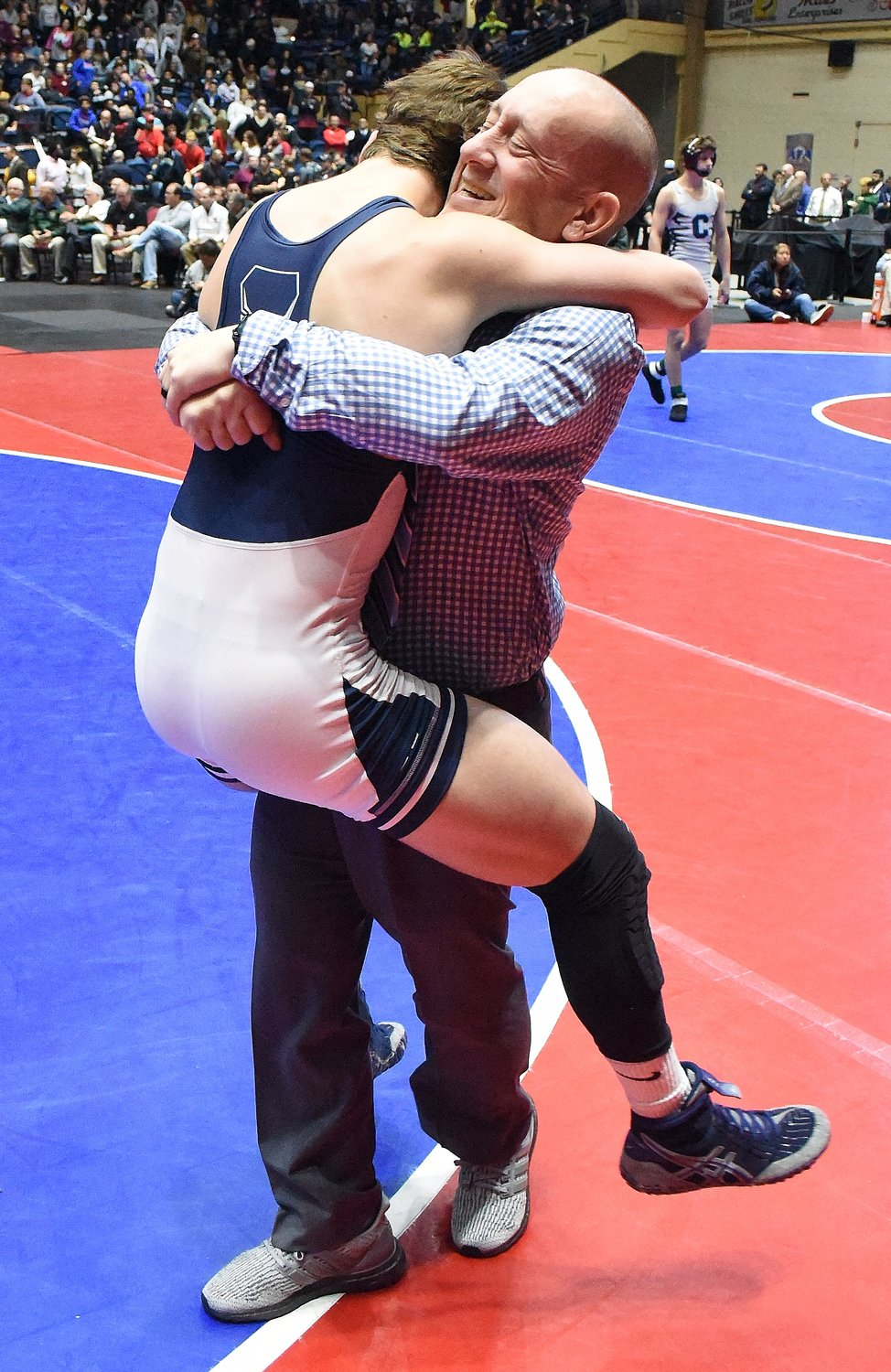 Woodland freshman wrestler Caden McCrary celebrates with coach Adrian Tramutola after McCrary won the Class 5A state title.