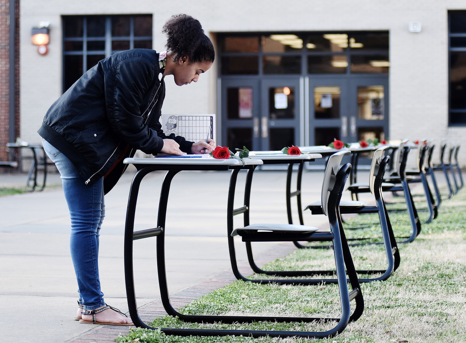 Cartersville High School senior Terrika Morris writes a letter to the family of one of the victims of the Feb. 14 shooting in Parkland, Florida. Seventeen desks were placed in the school's courtyard to represent the victims of the shooting. On each desk was a rose, a picture and name of a victim, and a notebook in which students could write messages to the families of the victims.