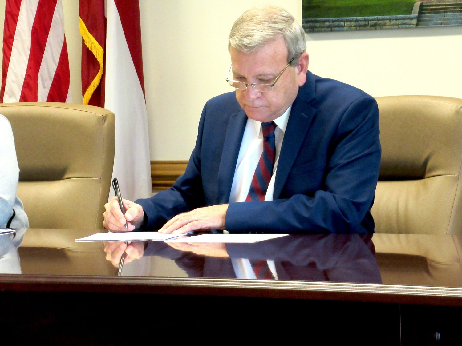 Bartow County Commissioner Steve Taylor inks paperwork at the first county commissioner meeting of the year.