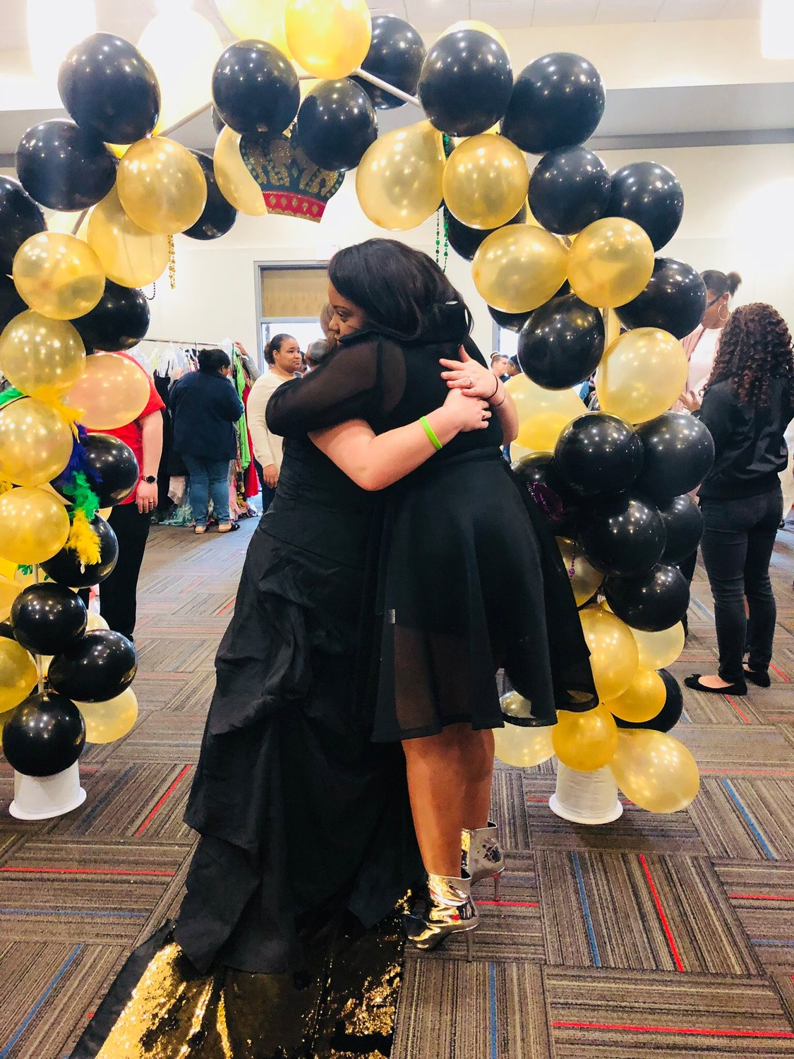 Scottlin Smith, Belles of the Ball's founder and director, embraces one of the event's recipients during the University of West Georgia offering Feb. 17, 2018.