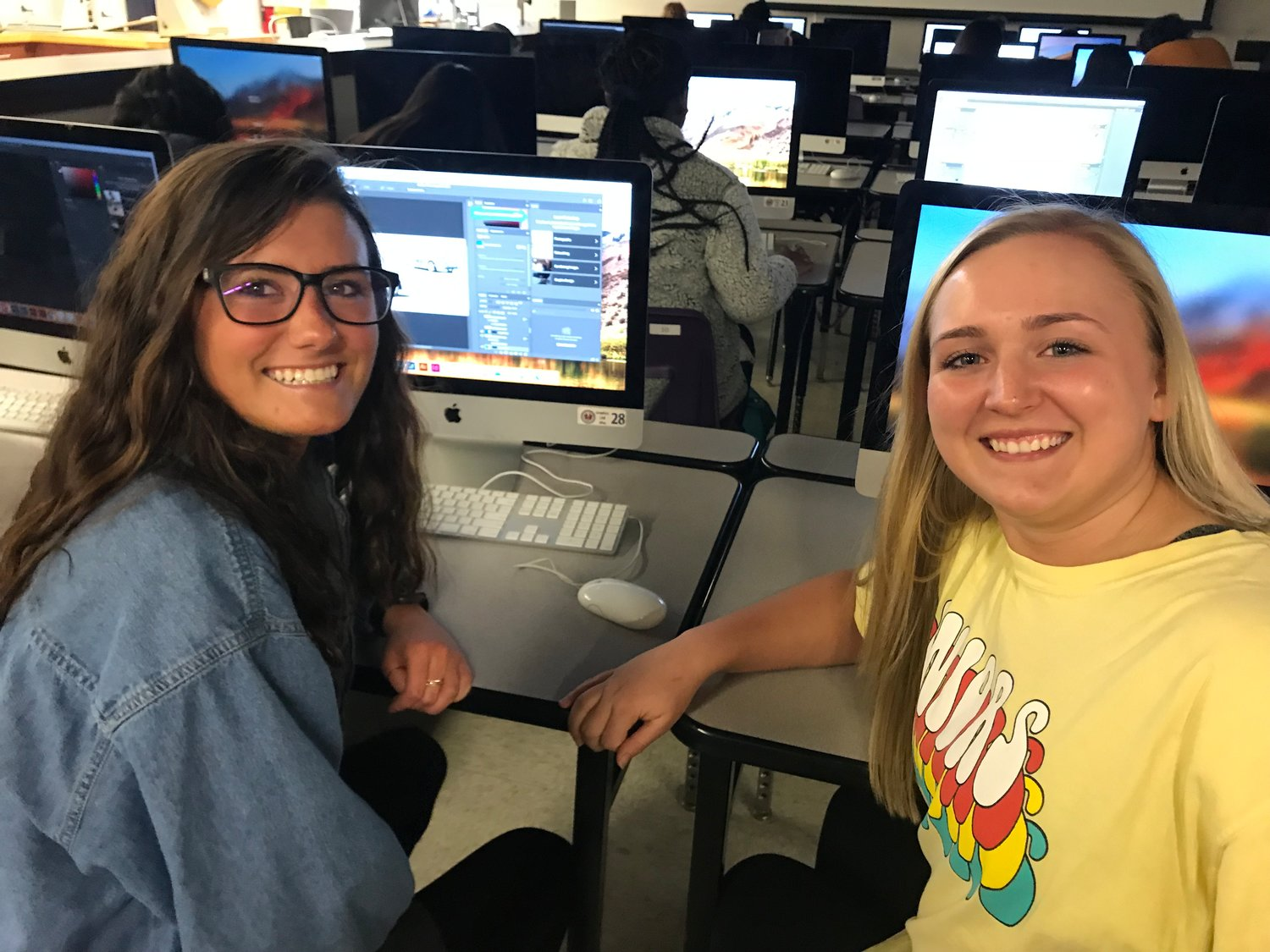 Cartersville High seniors Hattie Thompson, left, and Colbi Ballard work on creating a new design for the four patrol cars purchased last year by the Cartersville Police Department.