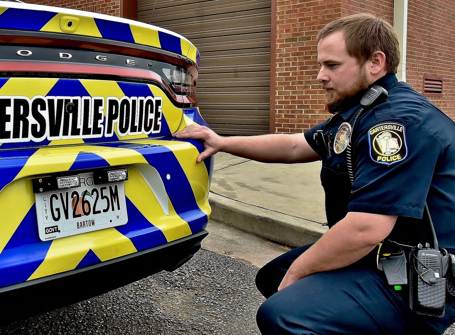 Officer Luke Pulliam of the Cartersville Police Department checks out the new design on the back of one of the department's four new cruisers.