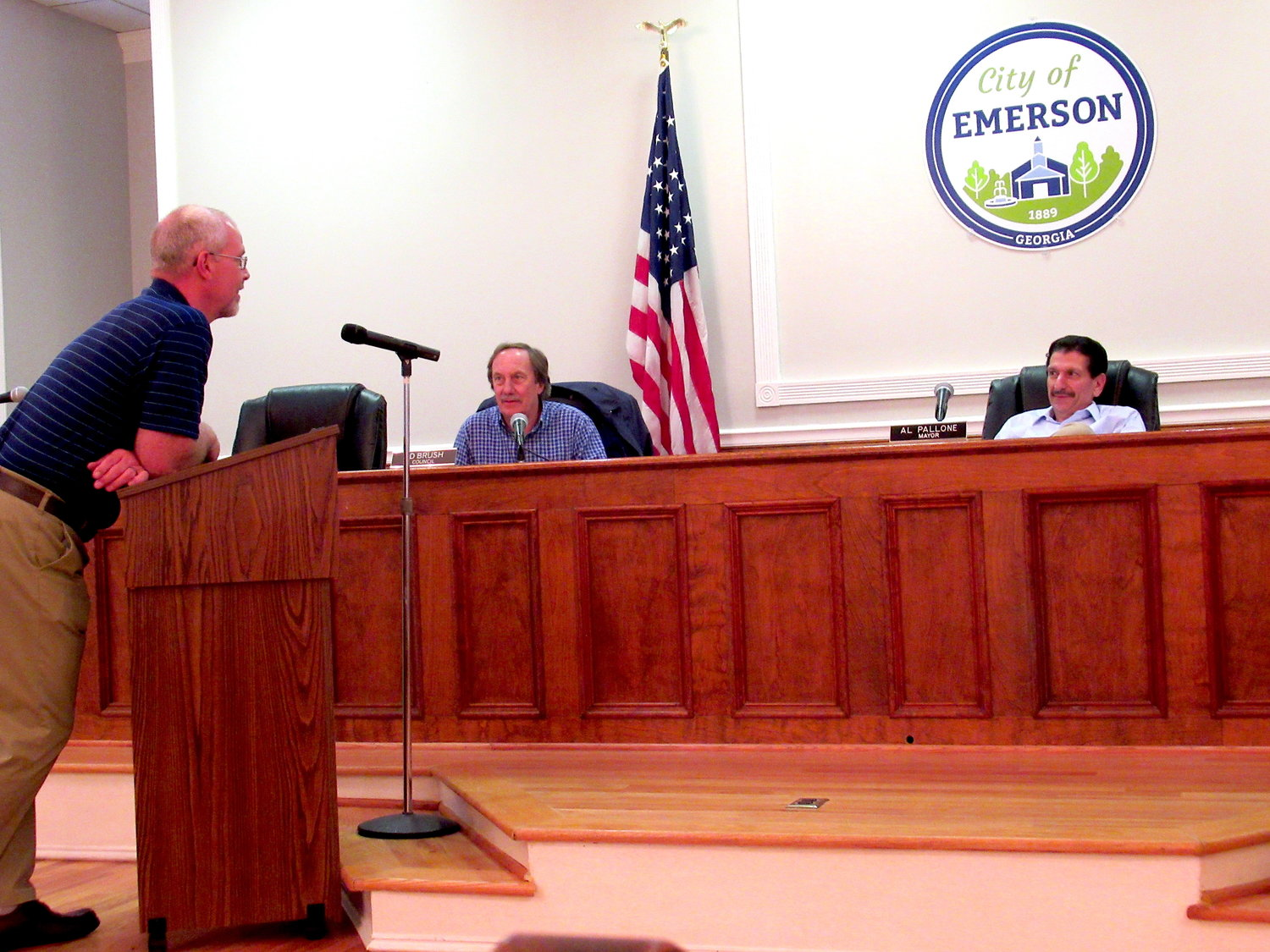 Emerson City Manager Kevin McBurnett takes to the podium at Monday's Emerson City Council meeting, with Councilman Ed Brush and Mayor Al Pallone in the background.