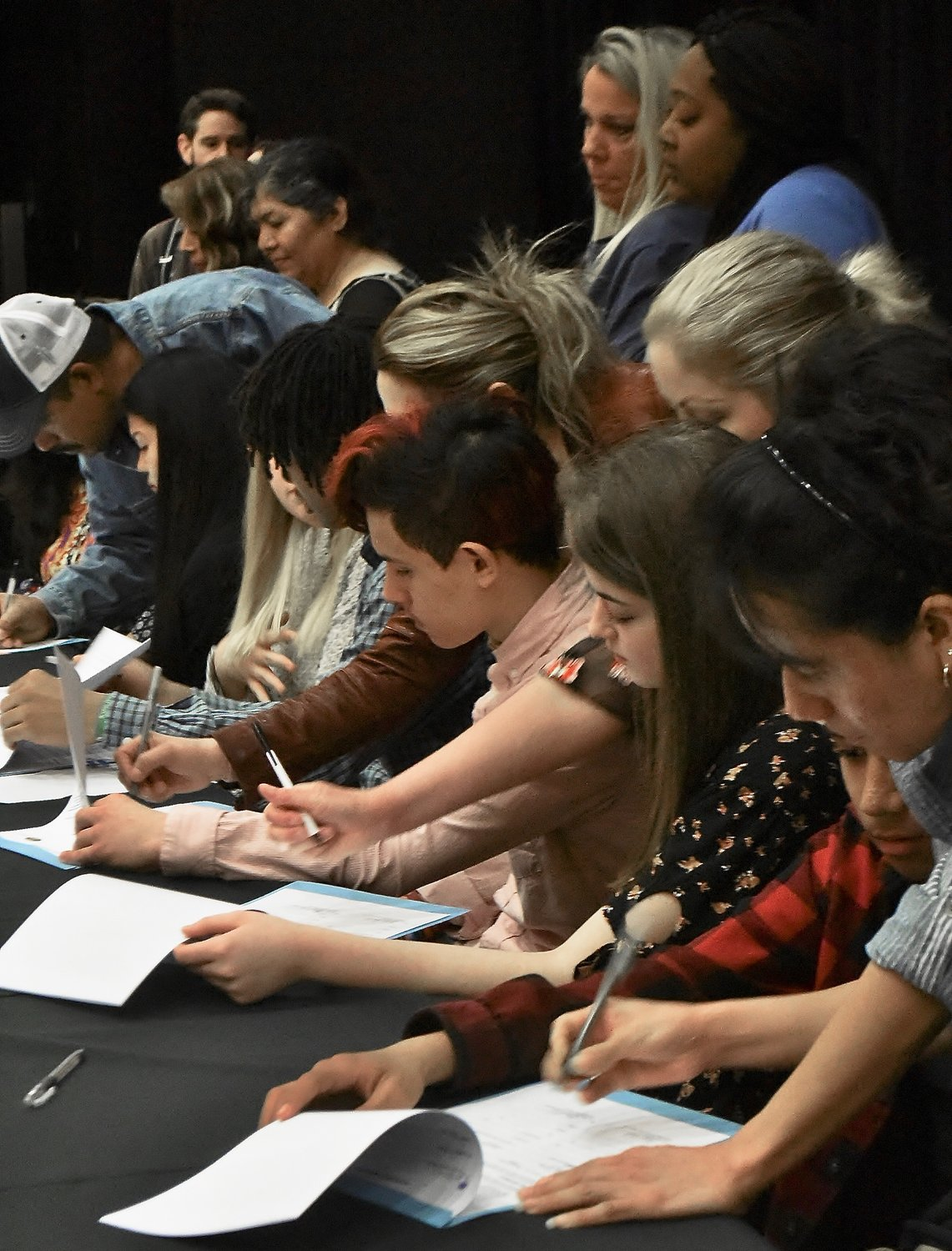 GateKey scholarship recipients and their parents sign their contracts at Friday morning's signing ceremony in the auditorium at Cartersville High School.