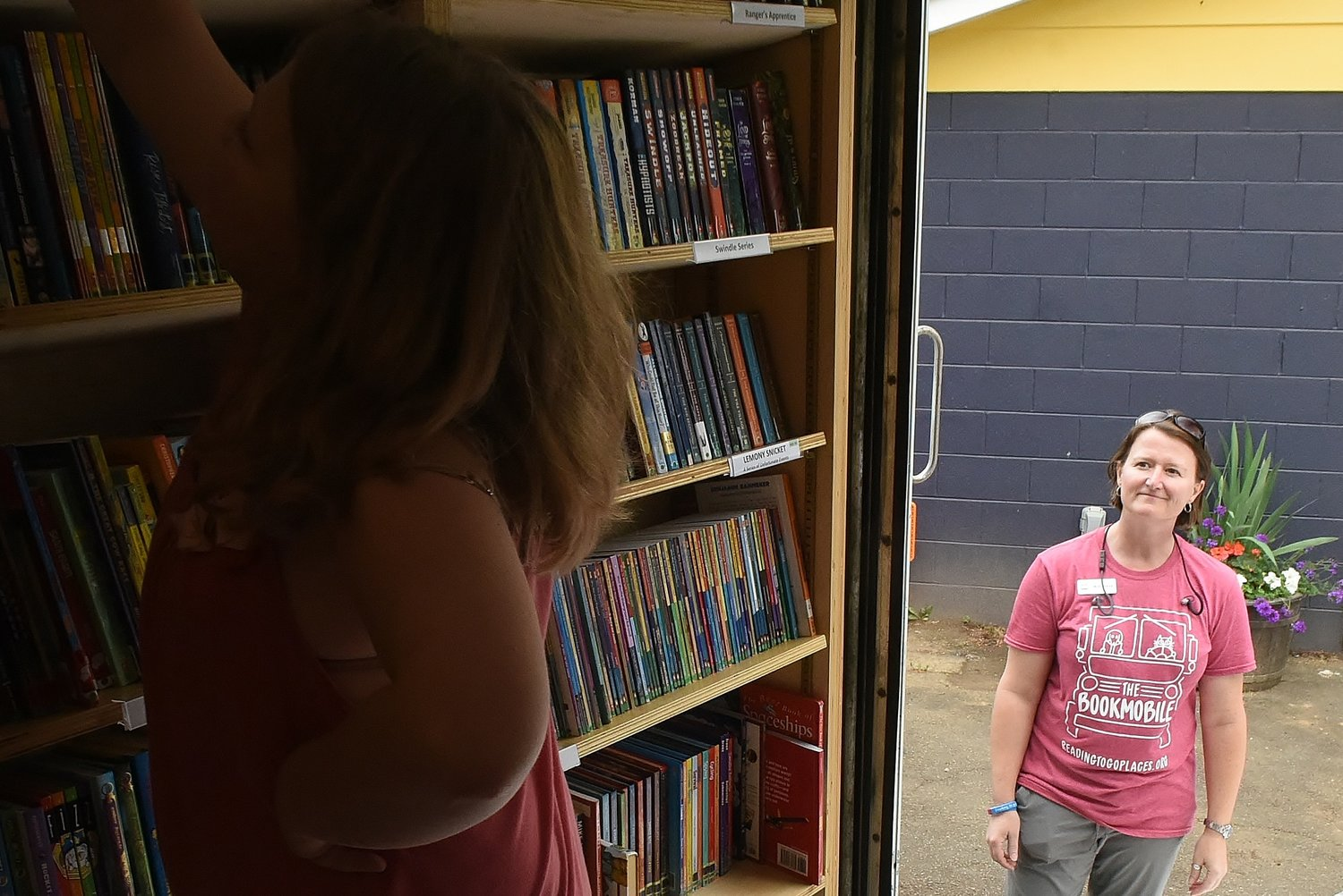Valerie Gilreath, founder of The Bookmobile, smiles as a young reader selects a book from the shelves of the mobile library at the SPARK Community Center Monday afternoon.