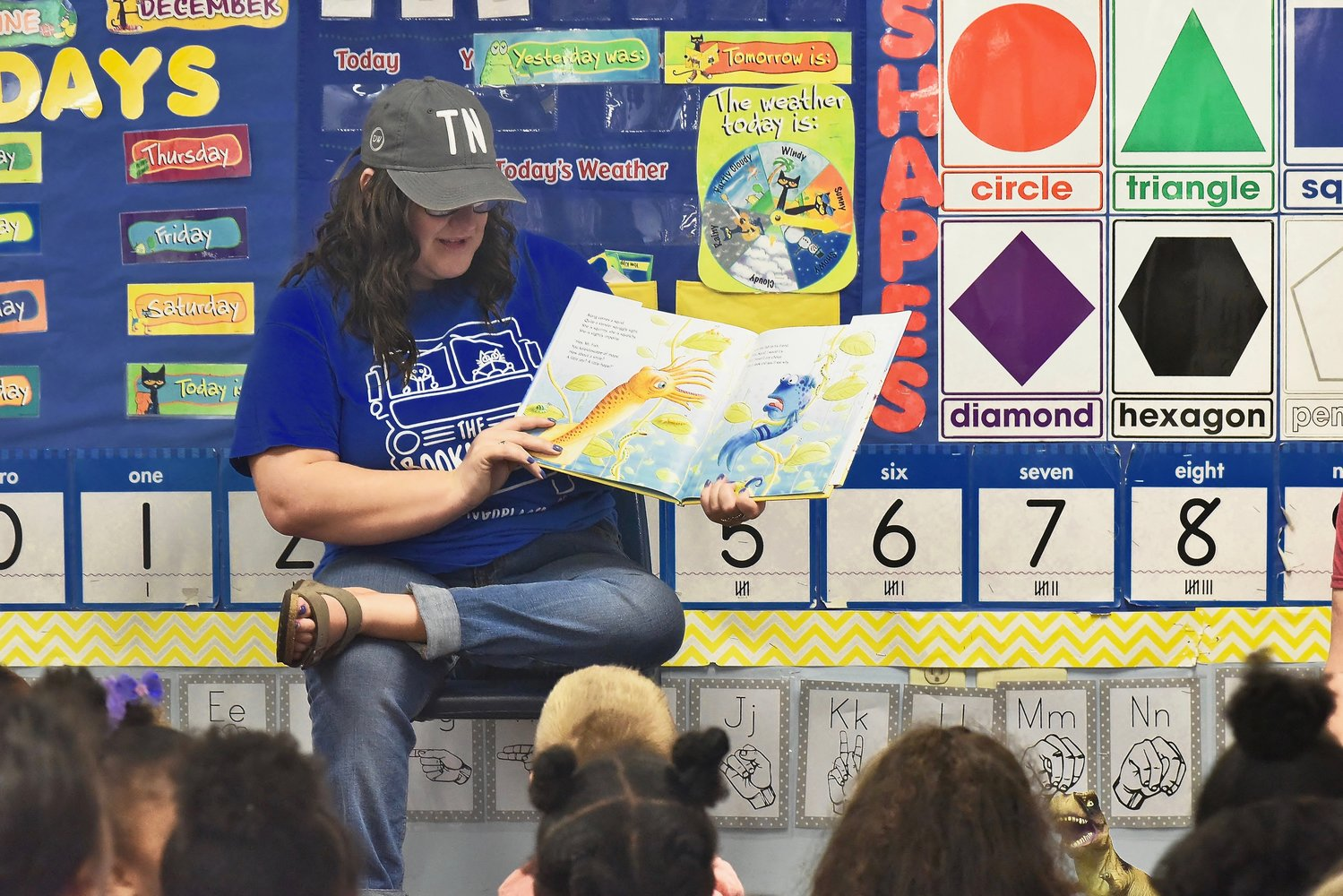Madison Cowart, a volunteer with The Bookmobile, reads to children Tuesday at Little Lambs Learning Center in Cartersville.