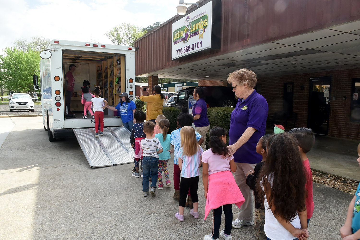 Students at Little Lambs Learning Center line up to visit The Bookmobile: Reading to Go Places! mobile library during Bookmobile Week in Bartow County.