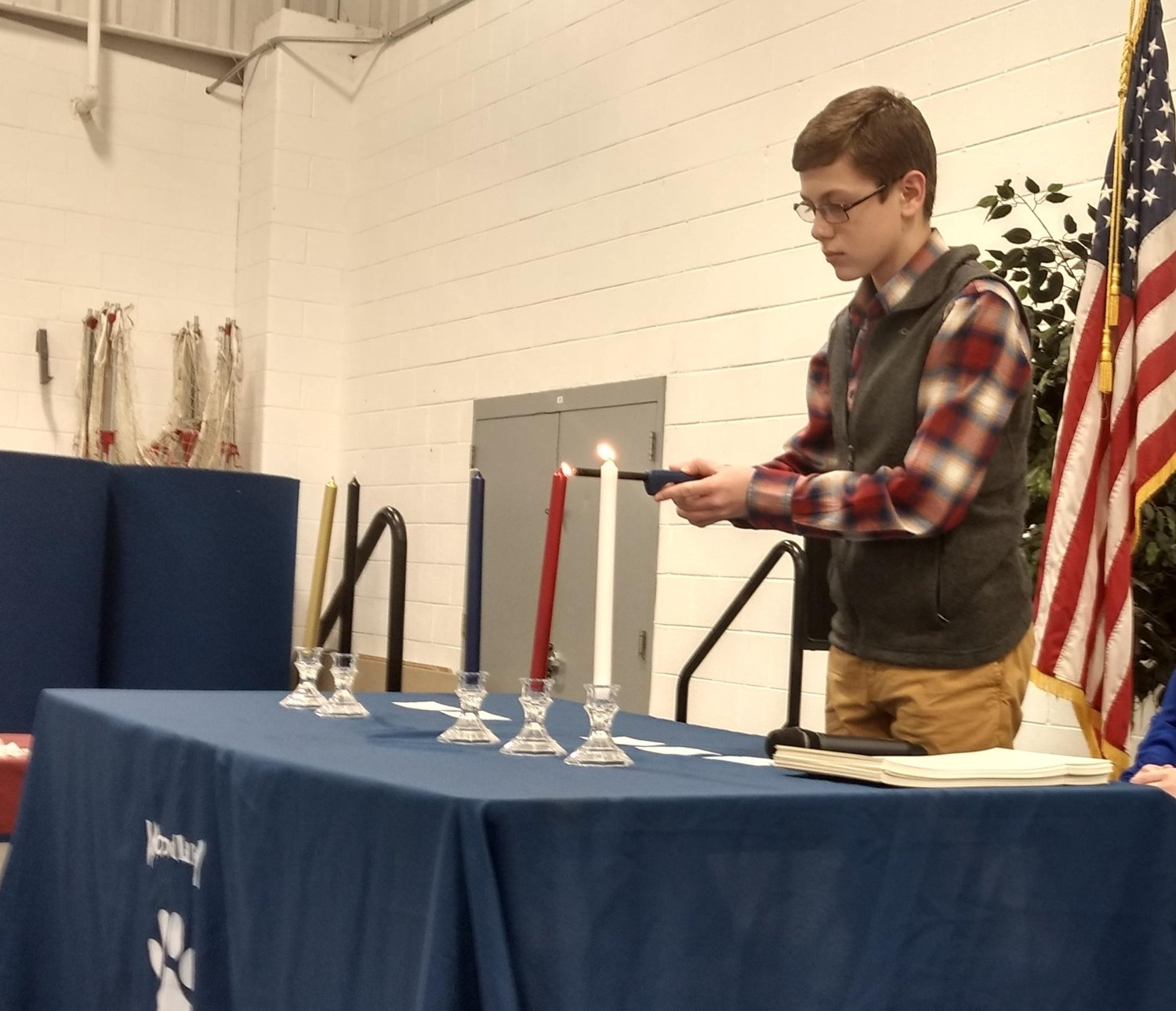 Woodland Middle eighth-grader Kameron Chappell lights the red candle of courage at the inaugural induction ceremony of the the school's National Junior Beta Club in February.