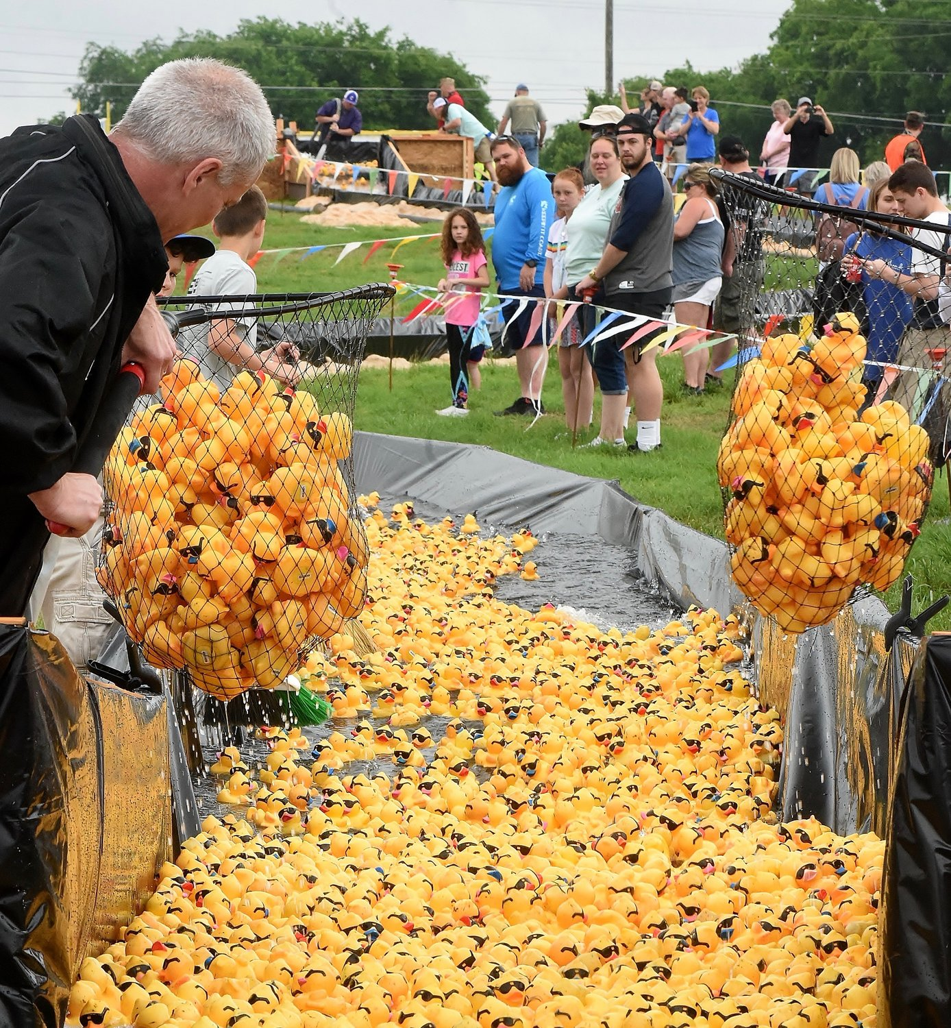 Large nets were used to remove ducks from the gathering pool at the bottom of the race course during Saturday's Duck Derby at Sam Smith Park.