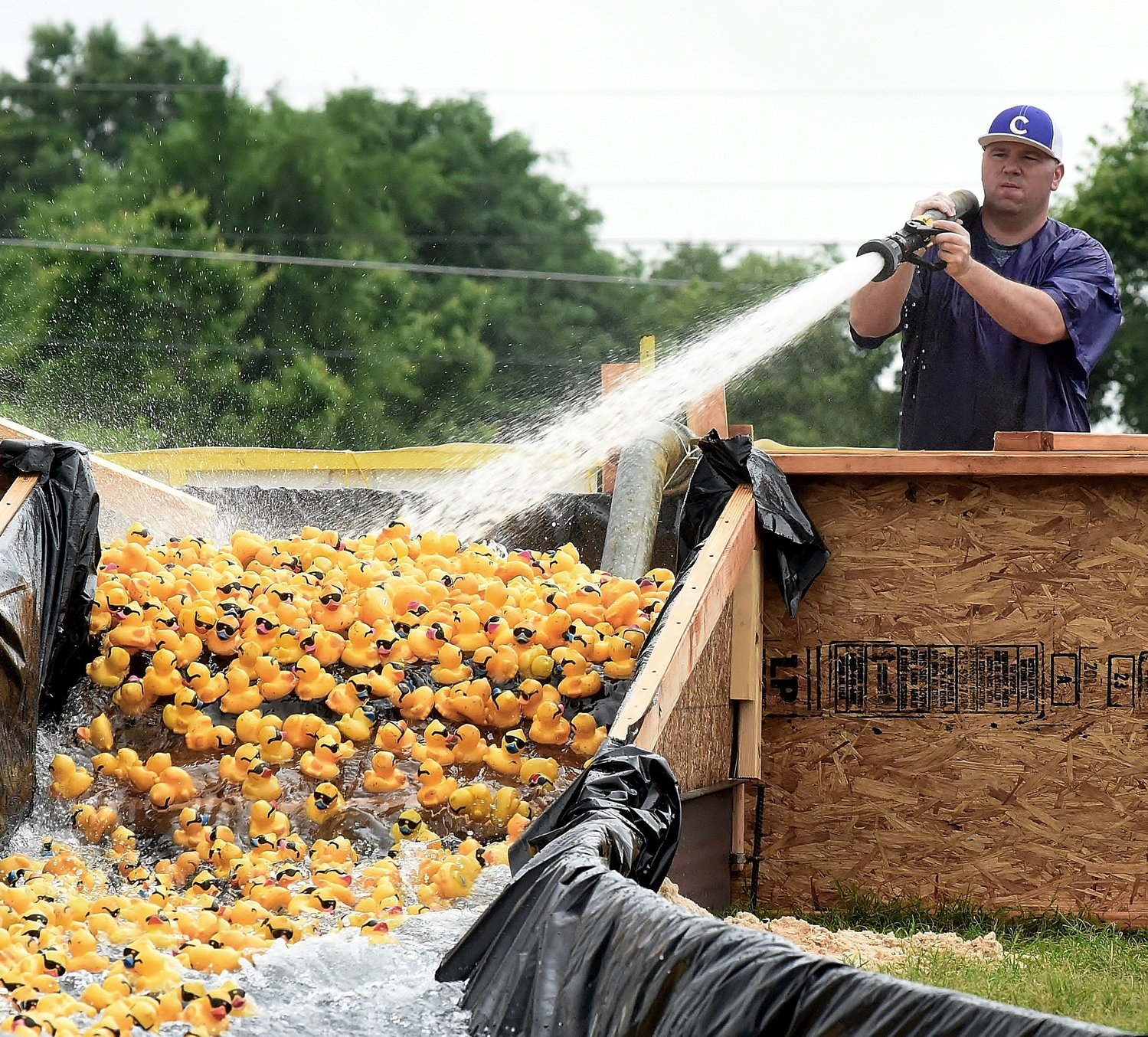 Using a high-powered water hose, a race official forces a round of ducks out of the pool at the top of the race course in Saturday's Duck Derby.