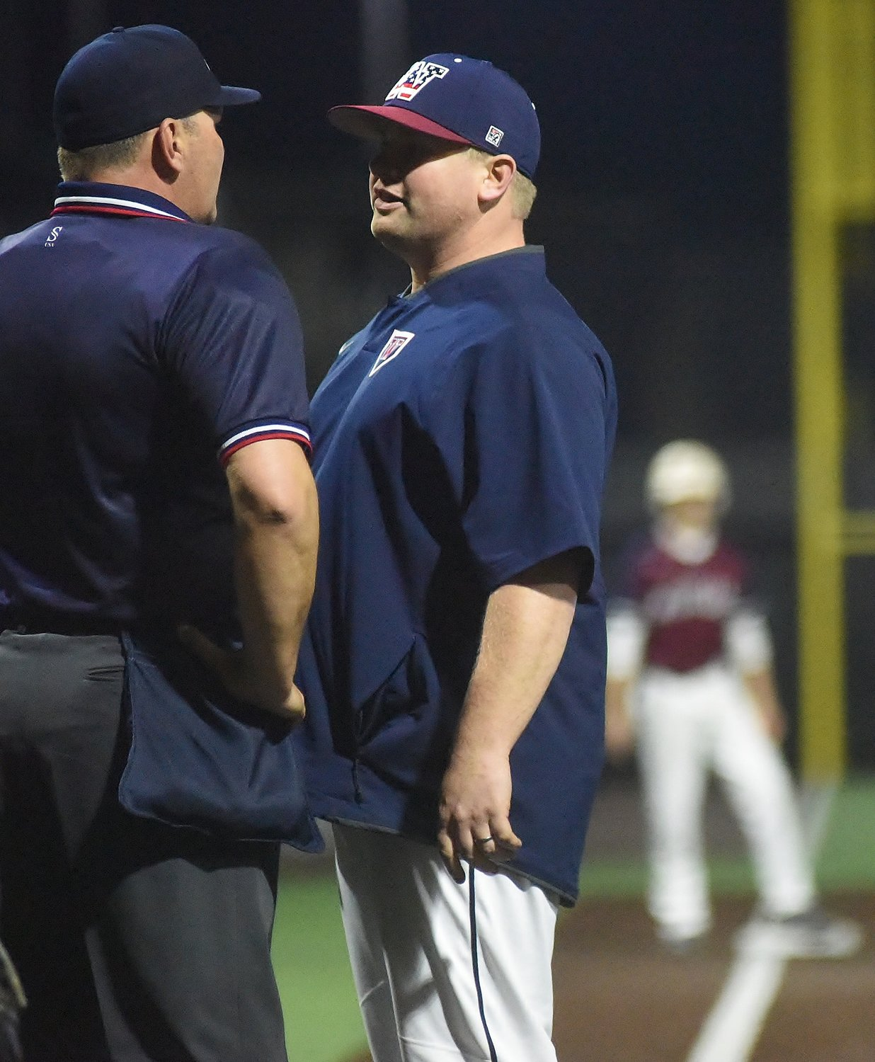 Matt Montgomery, right, speaks with an umpire during a Woodland High baseball game March 1 at LakePoint. Montgomery served as the Wildcats' interim head coach for a majority of the season before recently taking over the program on a permanent basis.