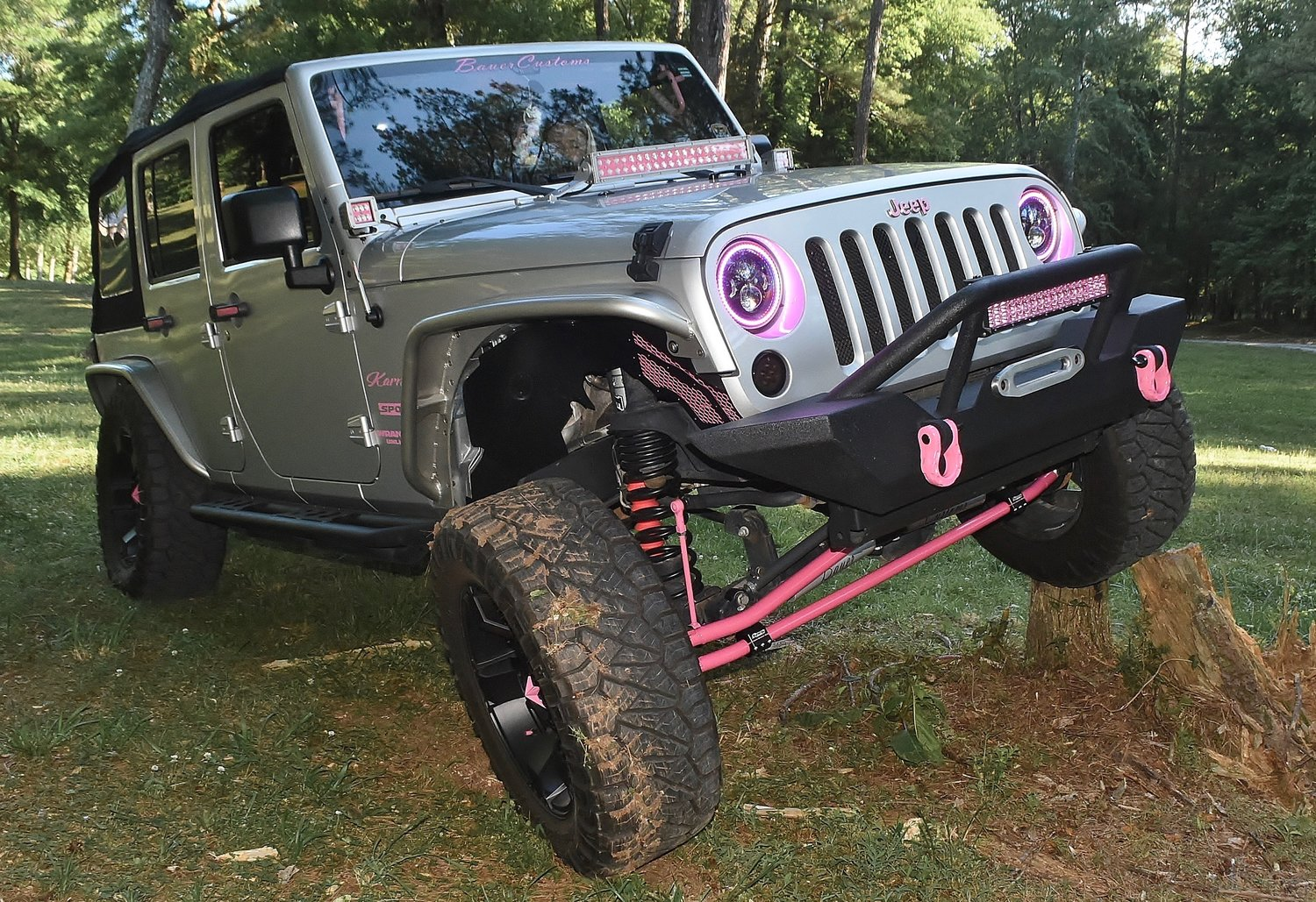 Bartow Krawlers member Kirstyn Bauer, flexing on a pair of stumps, has accessorized her Jeep with a number of pink accents.