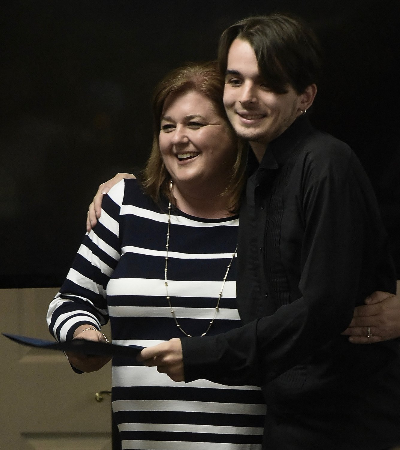 Project SEARCH instructor Jennifer Hyde gets a hug from intern River Southgate as she hands him his graduation certificate at the Project SEARCH graduation ceremony May 16 at Oakland Heights Baptist Church.